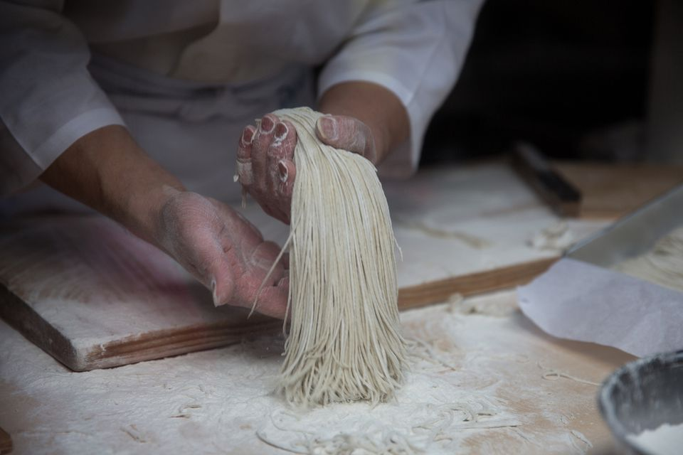 hands making noodles