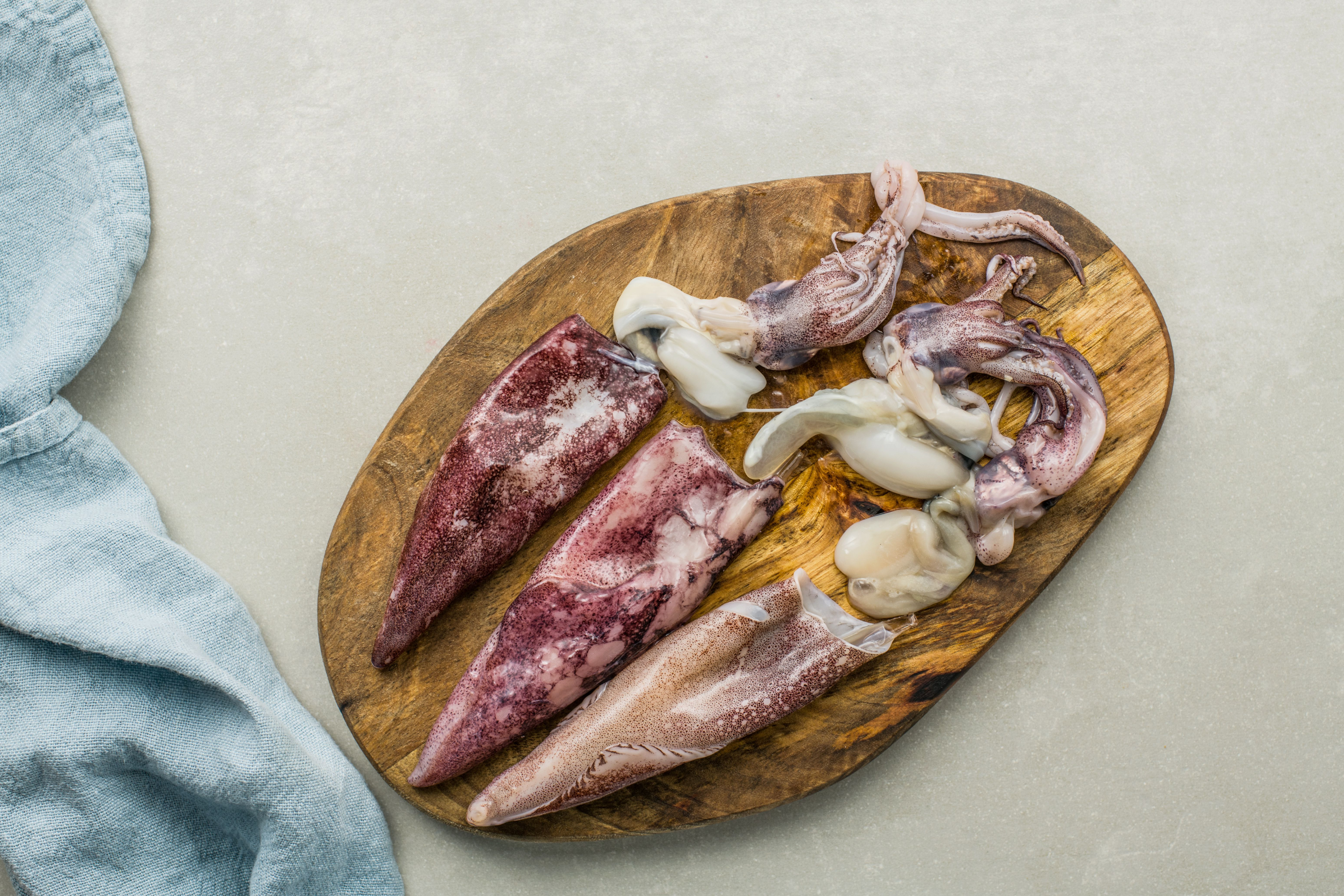Squid with heads removed on cutting board