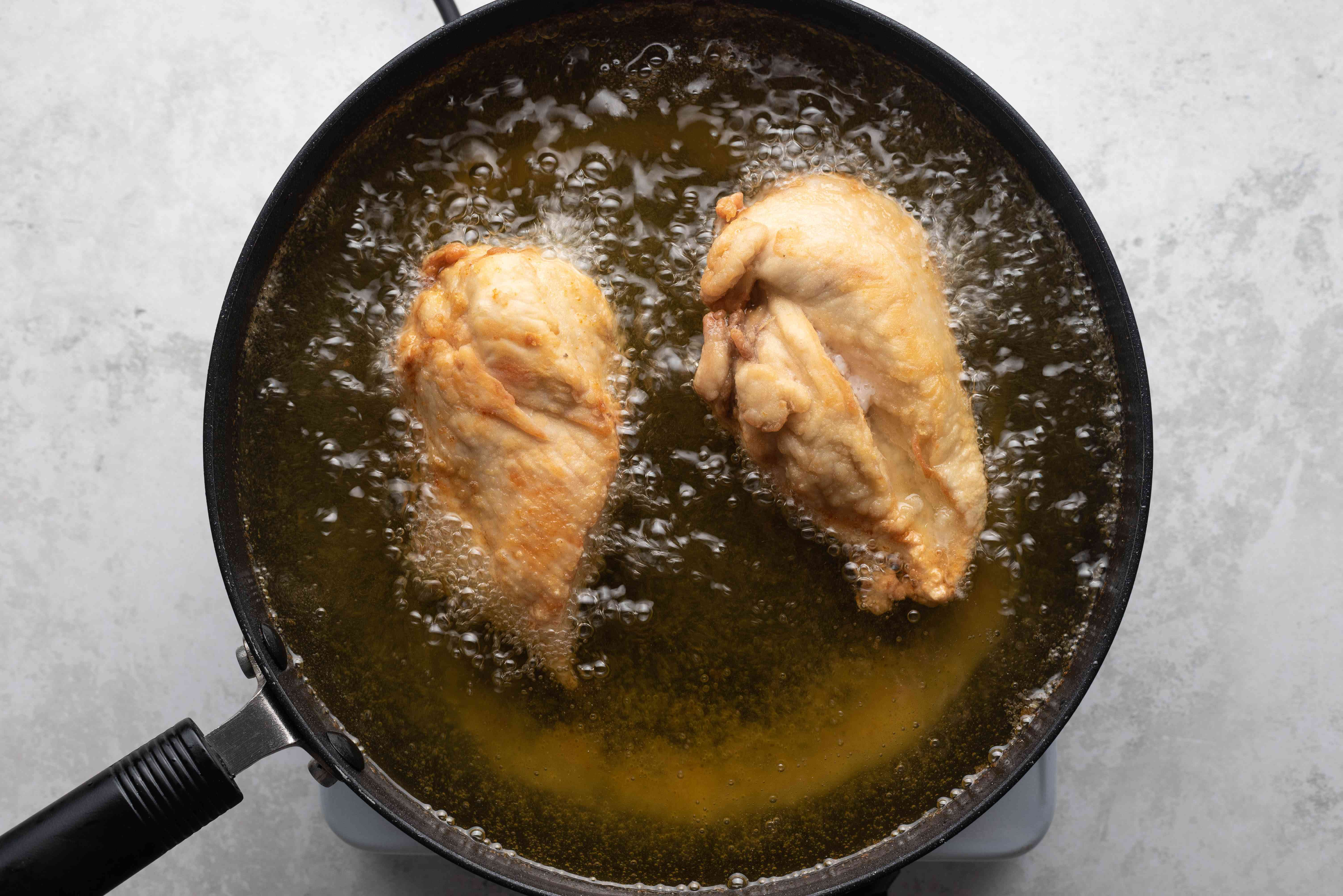 chicken cooking in a pot of oil