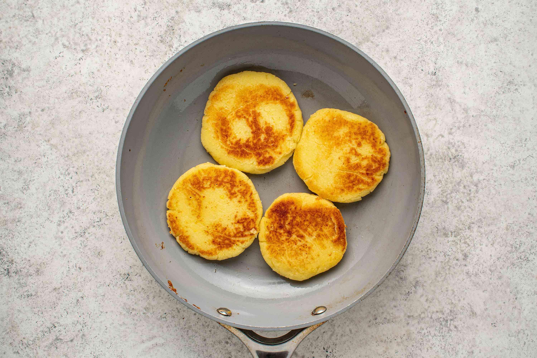 arepas cooking in a pan
