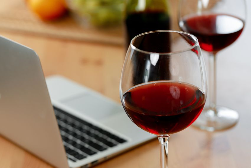 two glasses of red wine next to a laptop and a bottle of wine on a counter