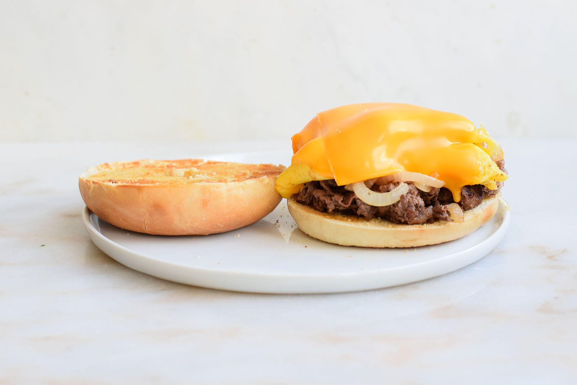 Bagel topped with steak, egg, and cheese