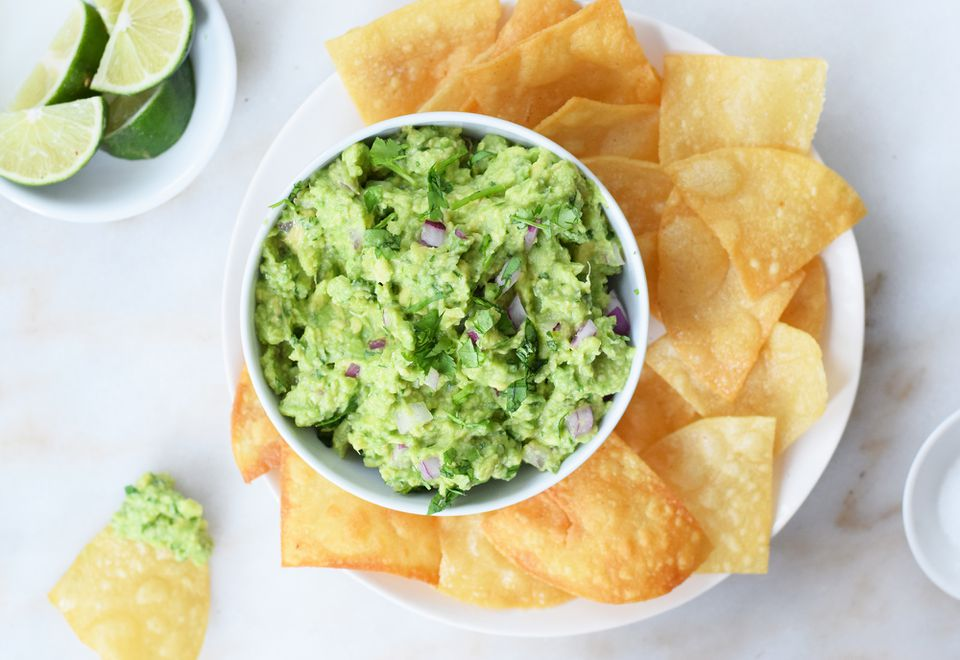 guacamole and chips on a plate with limes