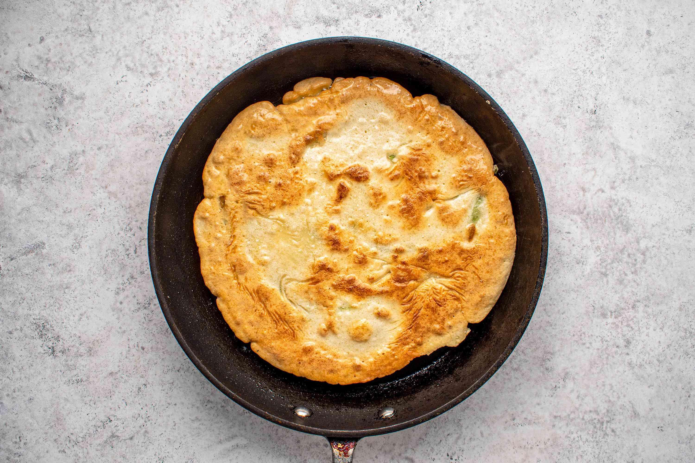 Pa jun (Korean scallion pancake) fully cooking in the pan