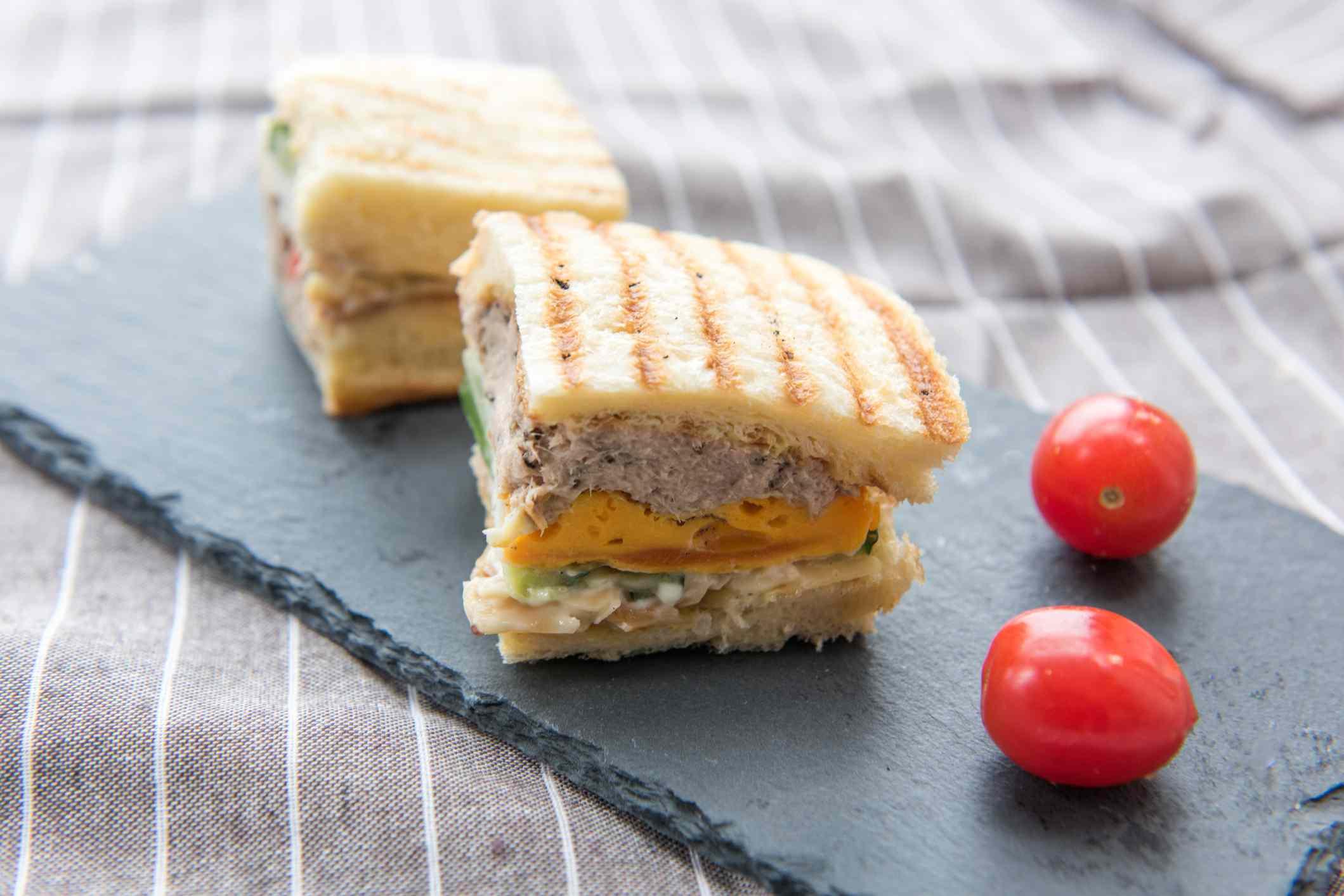 Tuna sandwiches on a slate board with grape tomatoes