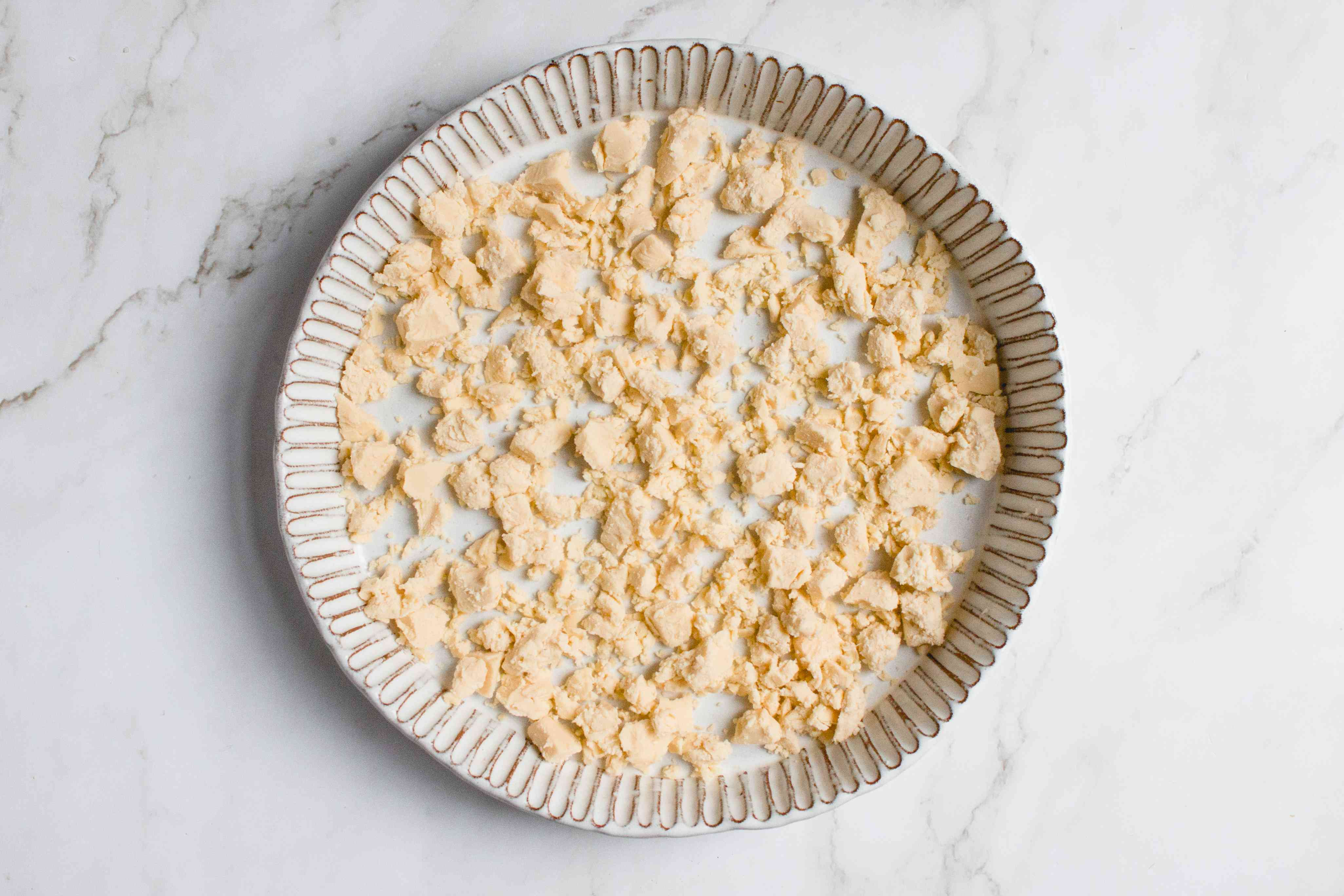 crumble dairy-free cheese into the bottom of a pie plate