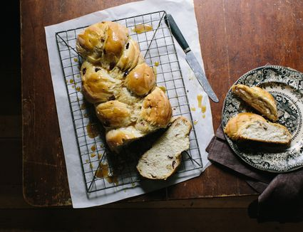 Sliced houska bread on a wire rack, parchment paper and a wooden surface