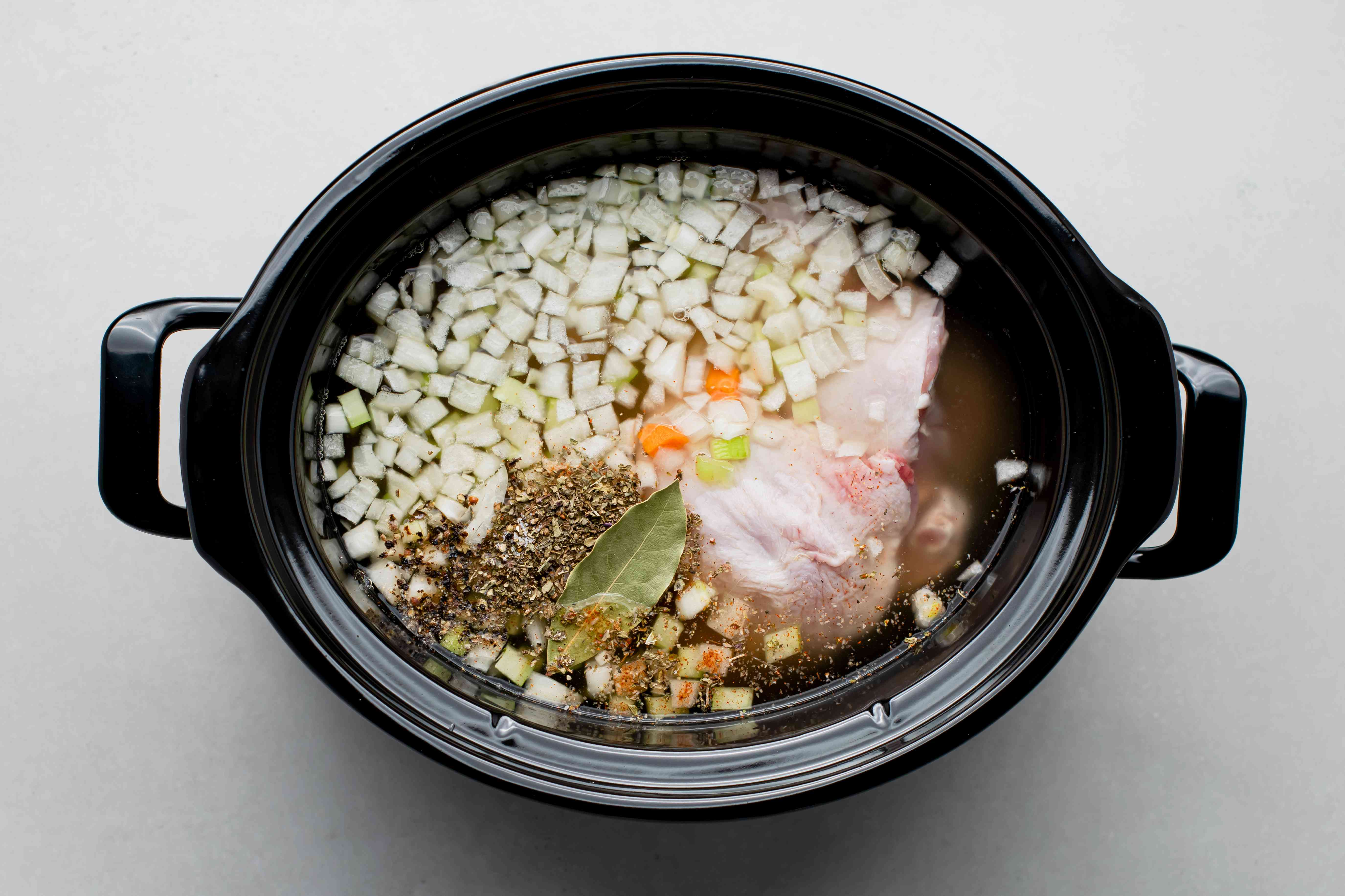 all of the ingredients for Crock Pot Chicken Noodle Soup (except the noodles) in a Crock Pot