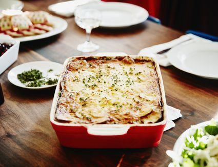 Roasted scalloped potatoes in pan on table for holiday meal