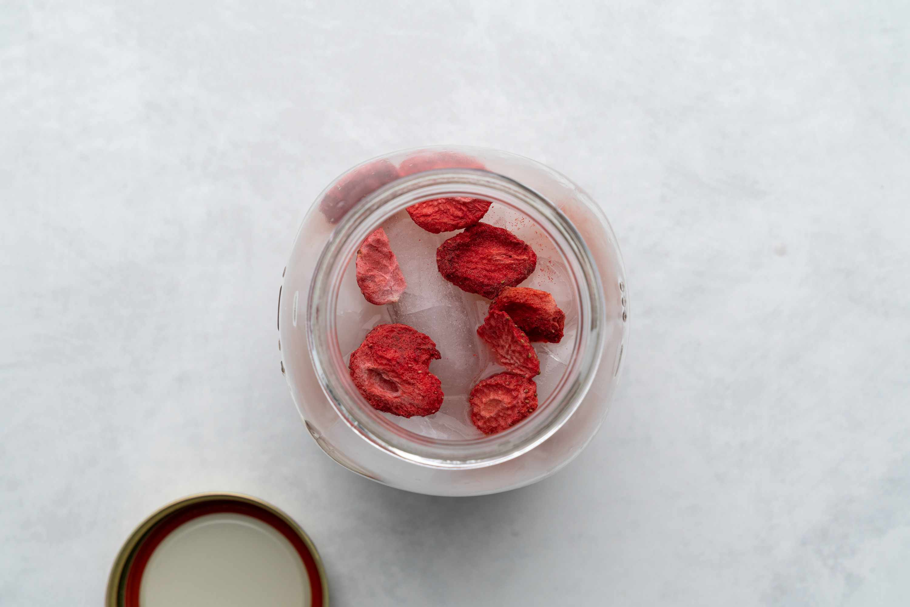 Pink Drink in a mason jar topped with freeze-dried strawberries