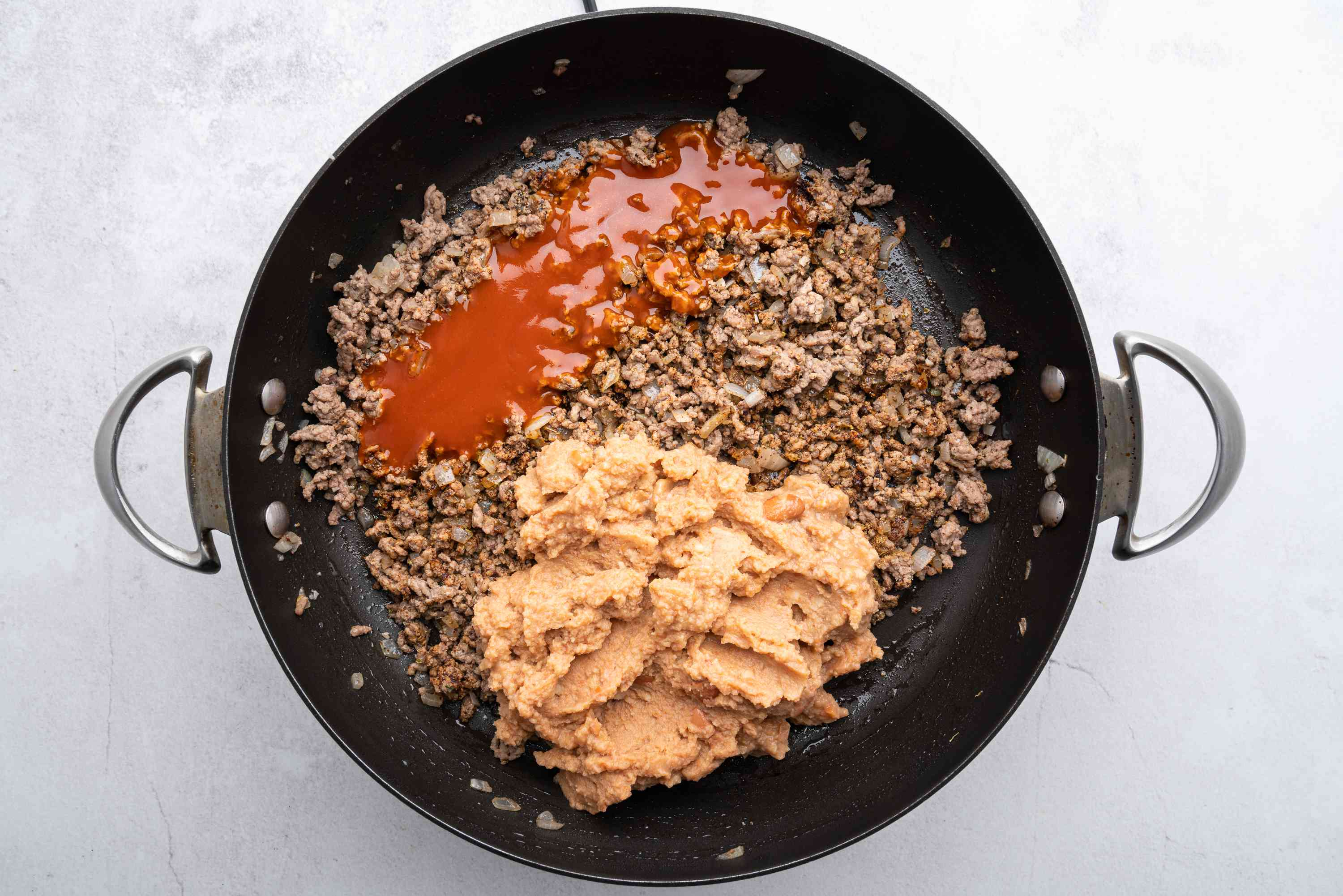 refried beans and enchilada sauce with the beef mixture in the skillet