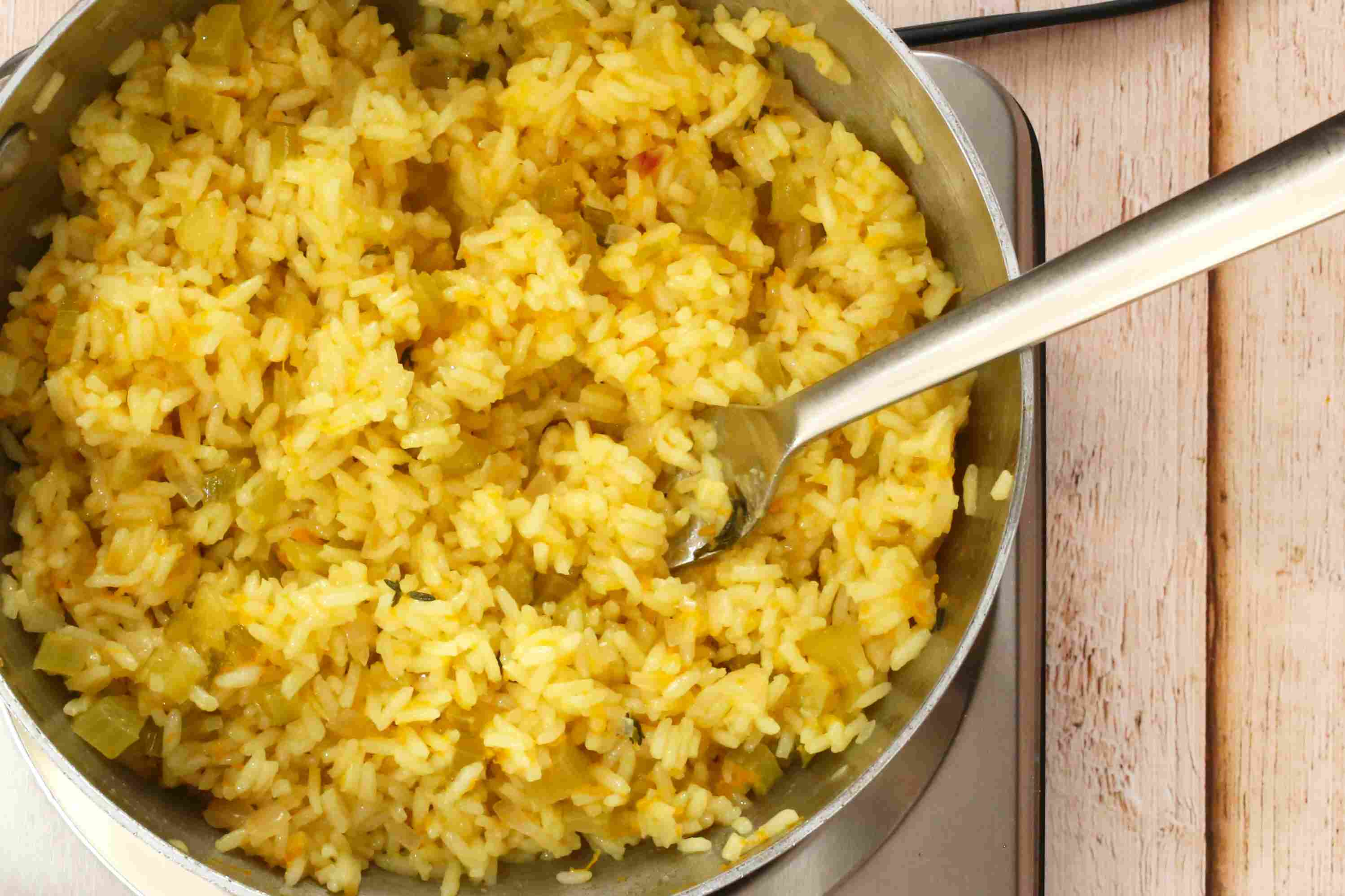 Fluff the orange rice with a fork.