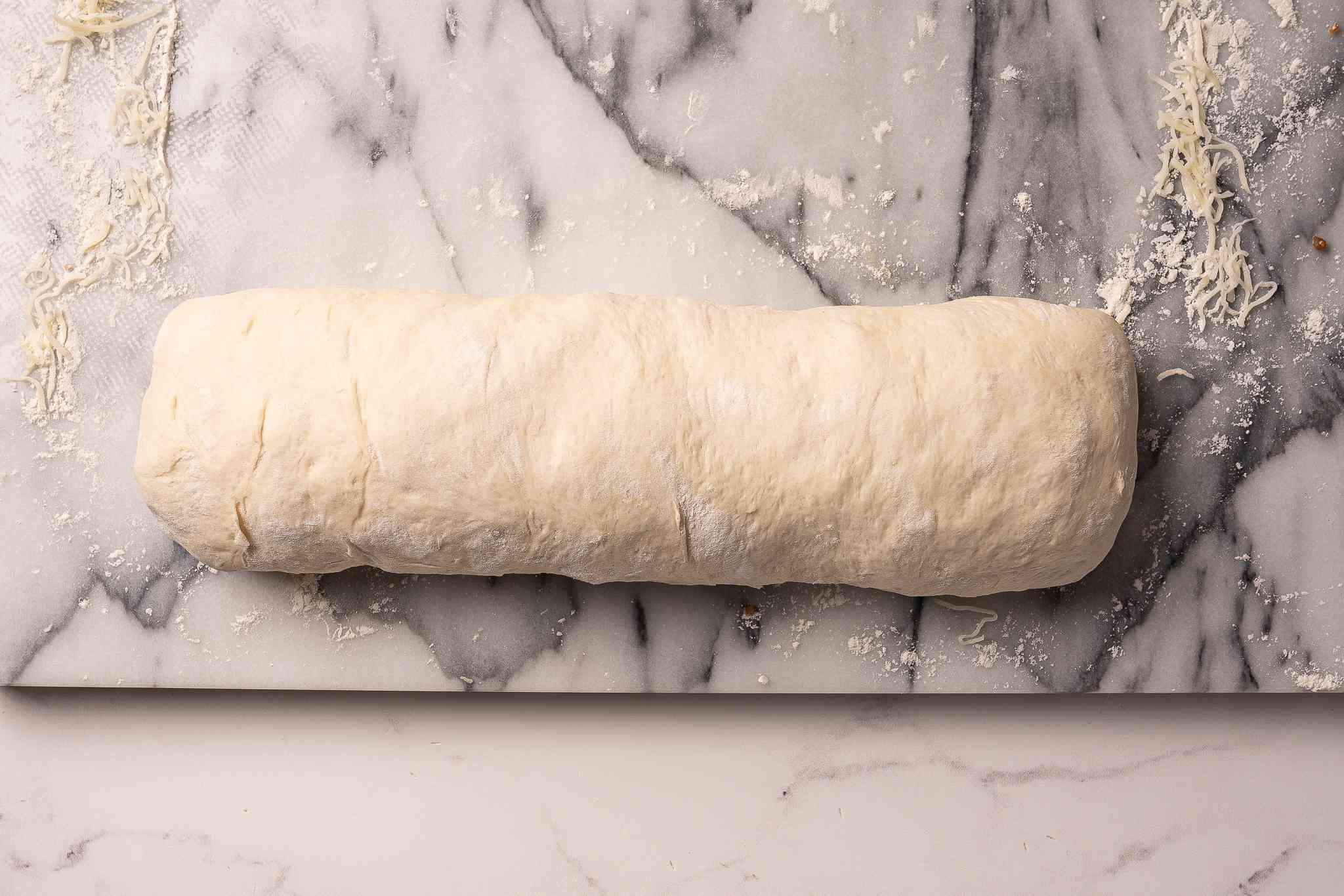Dough rolled into a log with sausage and cheese inside