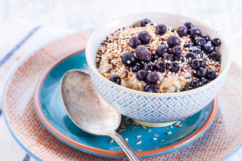 Vegan superfood breakfast with porridge, almond milk, blueberries and roasted quinoa