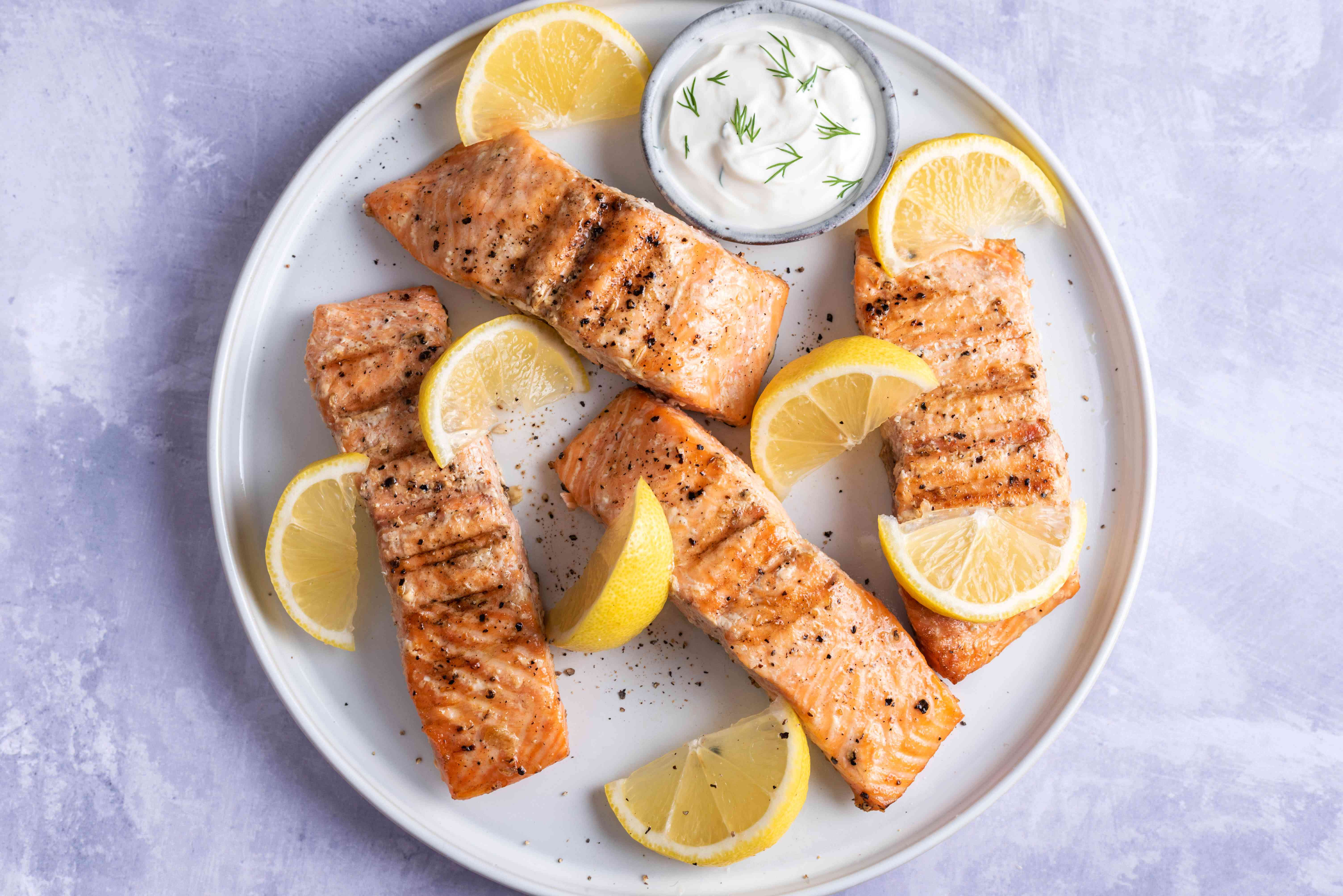 Grilled salmon with lemon wedges