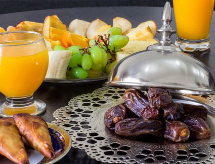 Regional Food Backgrounds. Dried date palm fruits, fresh orange juice, samosa snack and blurred fruit background concept iftar in the holy month Ramadan.