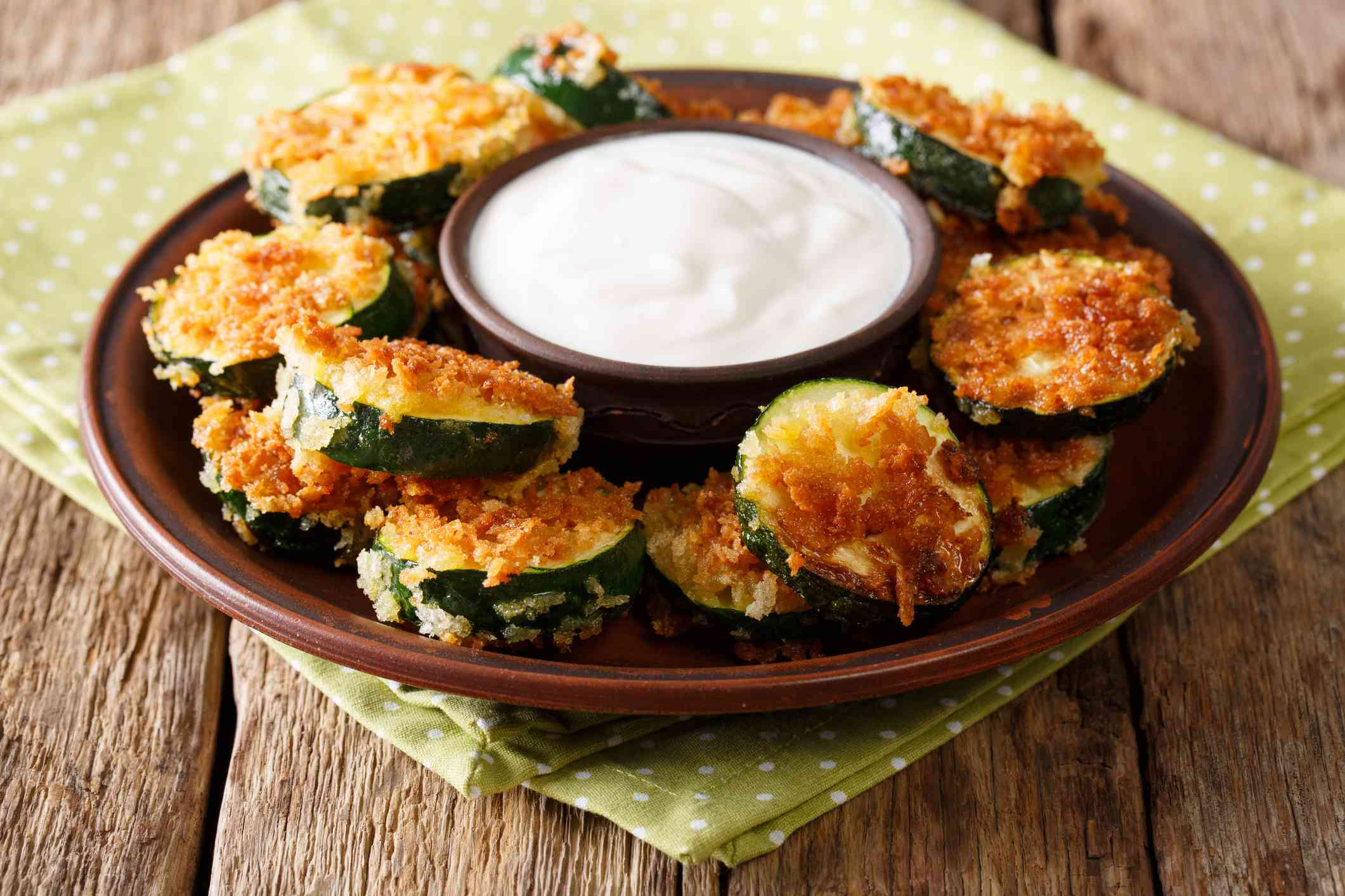 Homemade zucchini slices in breadcrumbs with sour cream close-up. horizontal