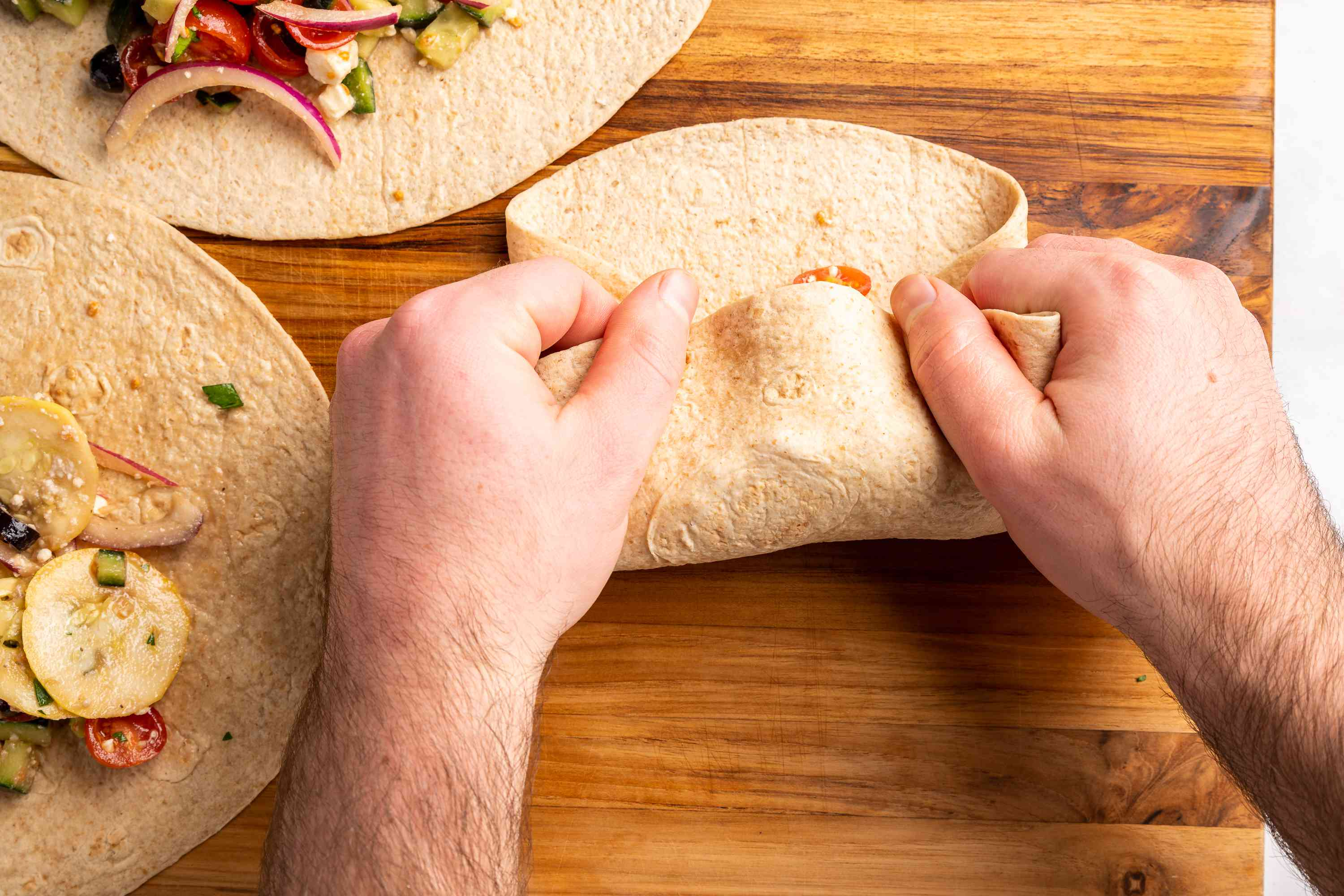 Hands rolling up tortilla into wrap shape