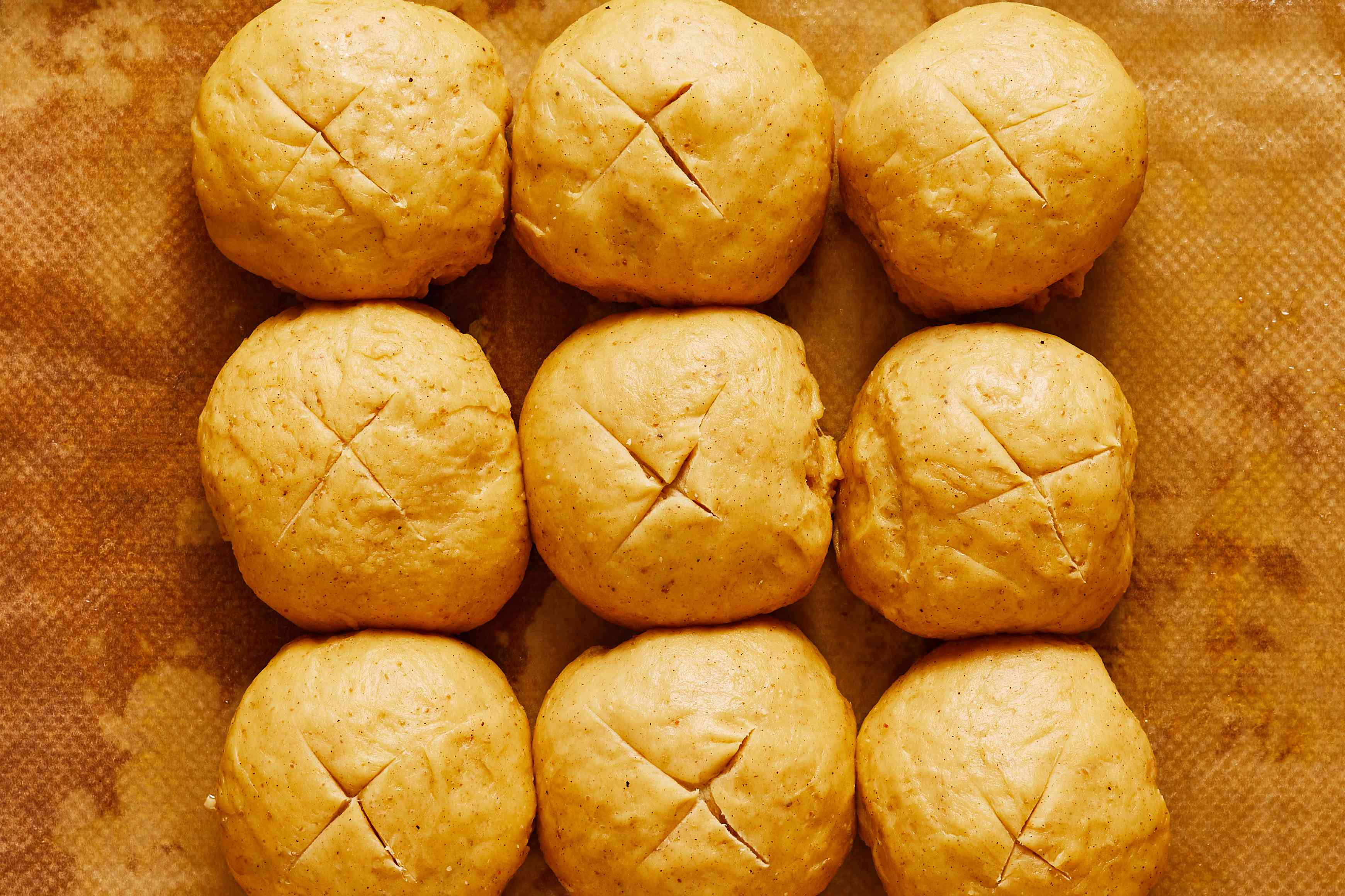 risen dough balls on baking sheet with an X marked on top
