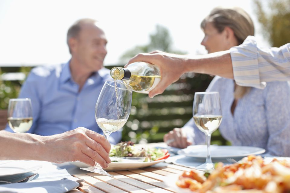 Man pouring wine at sunny table