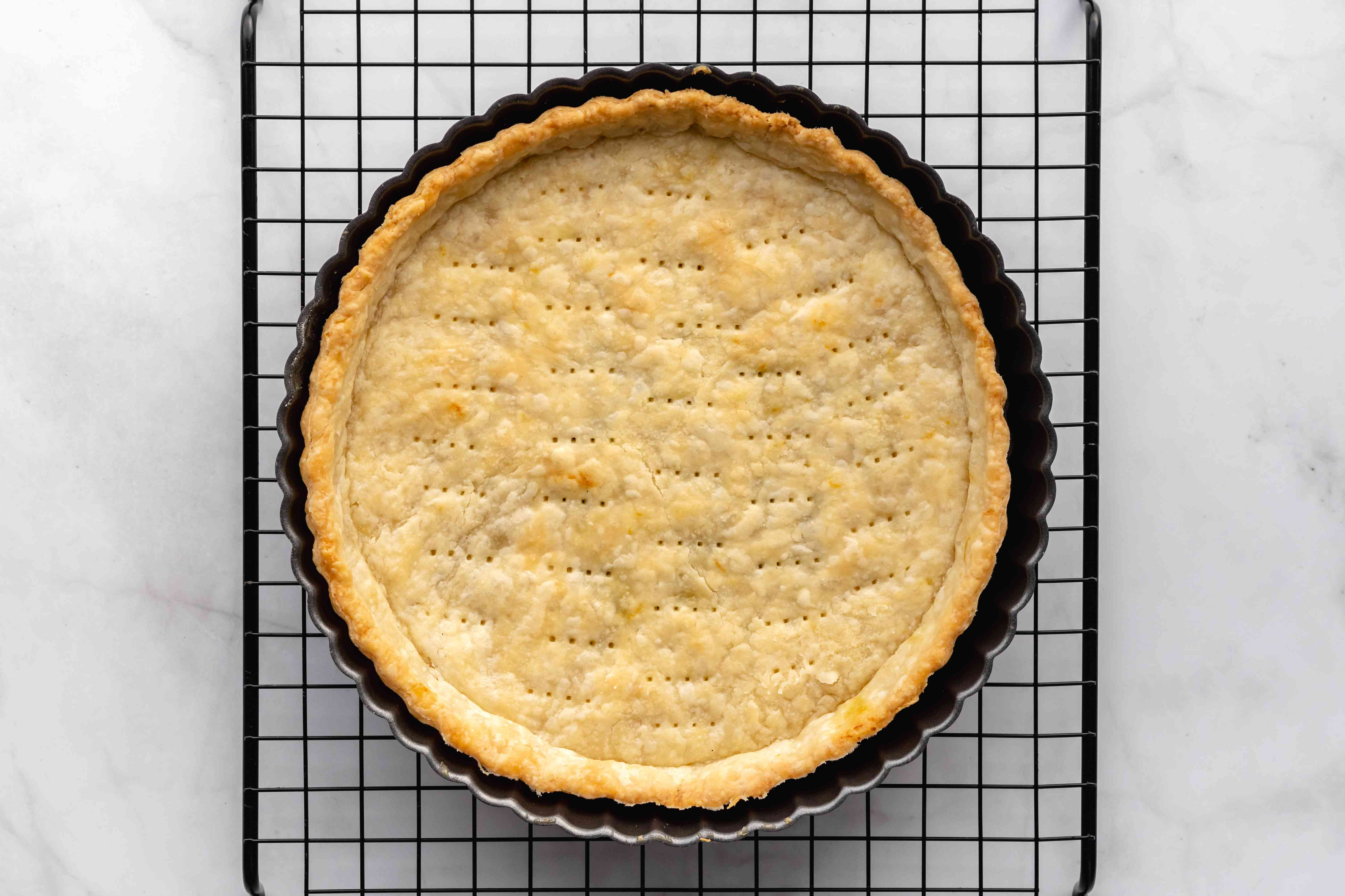 baked tart dough in a tart pan cooling on a cooling rack