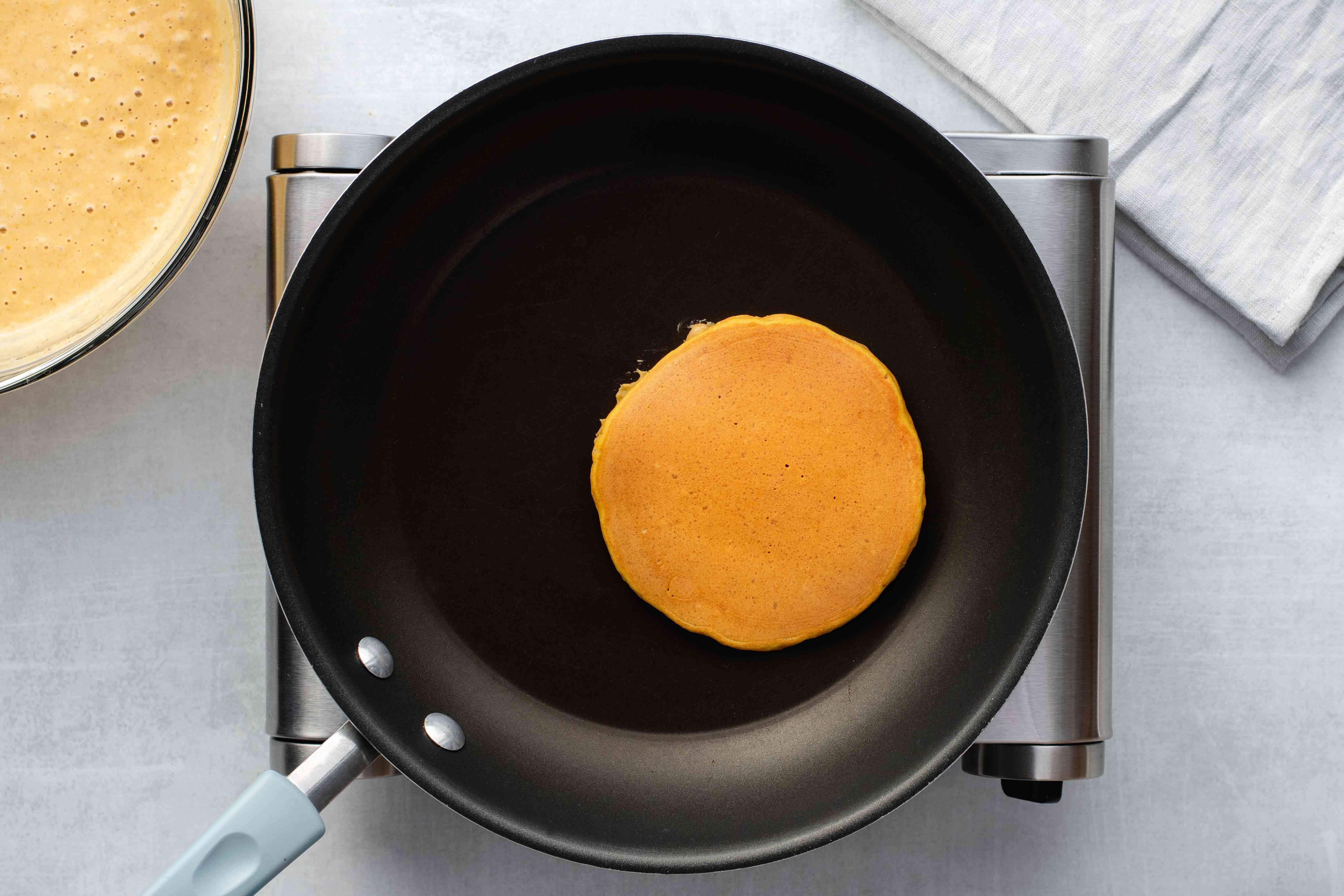 Pumpkin pancake cooking in the pan
