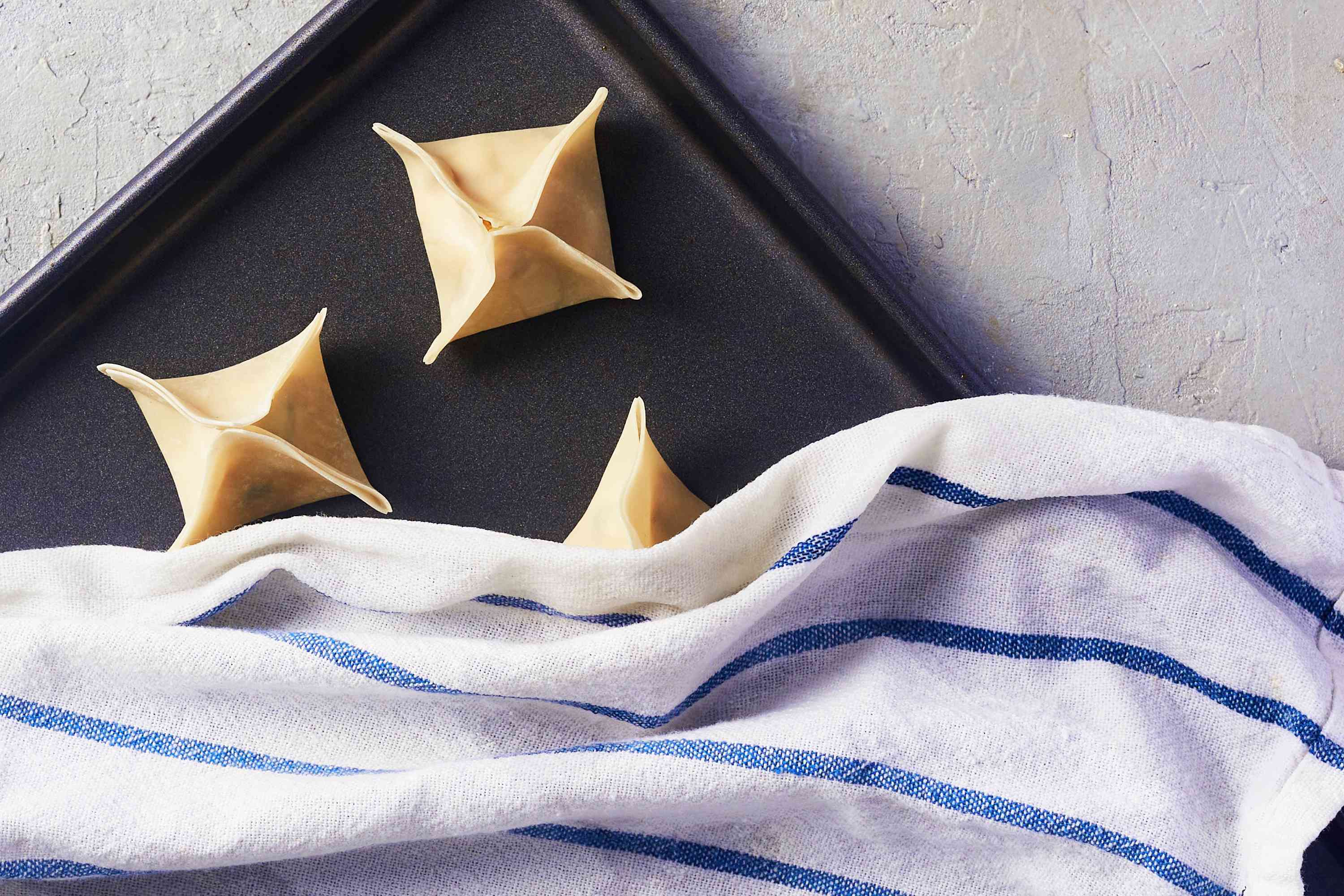 crab rangoon on a sheet pan covered with a towel