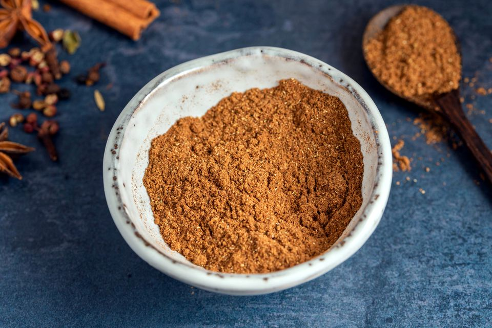 Five spice powder in a white bowl and on a wooden spoon