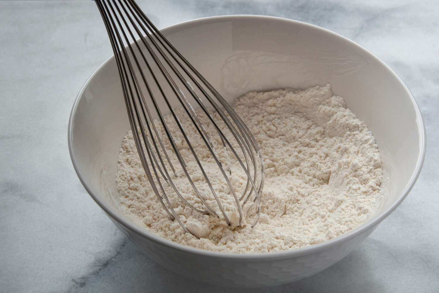 Flour and baking powder in a white mixing bowl, metal whisk