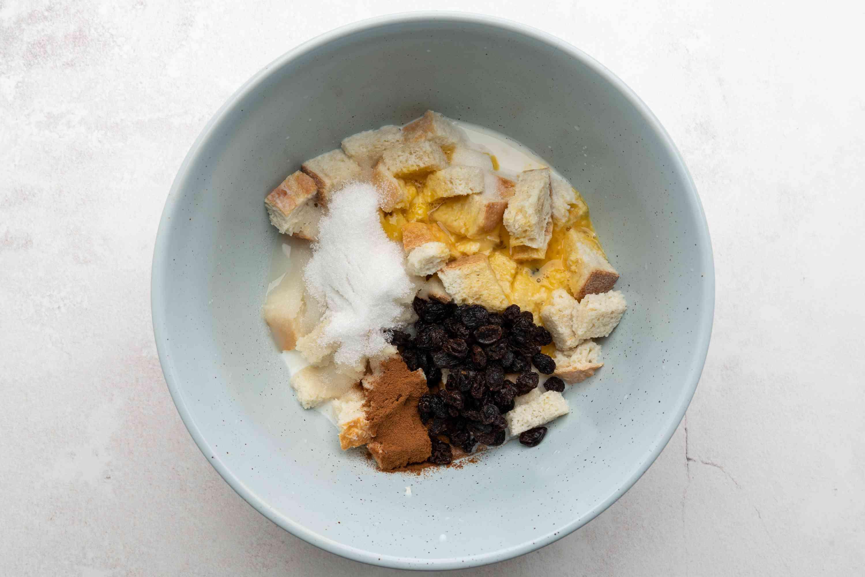 sugar, salt, nutmeg or cinnamon, eggs, and raisins added to the bread mixture in the bowl
