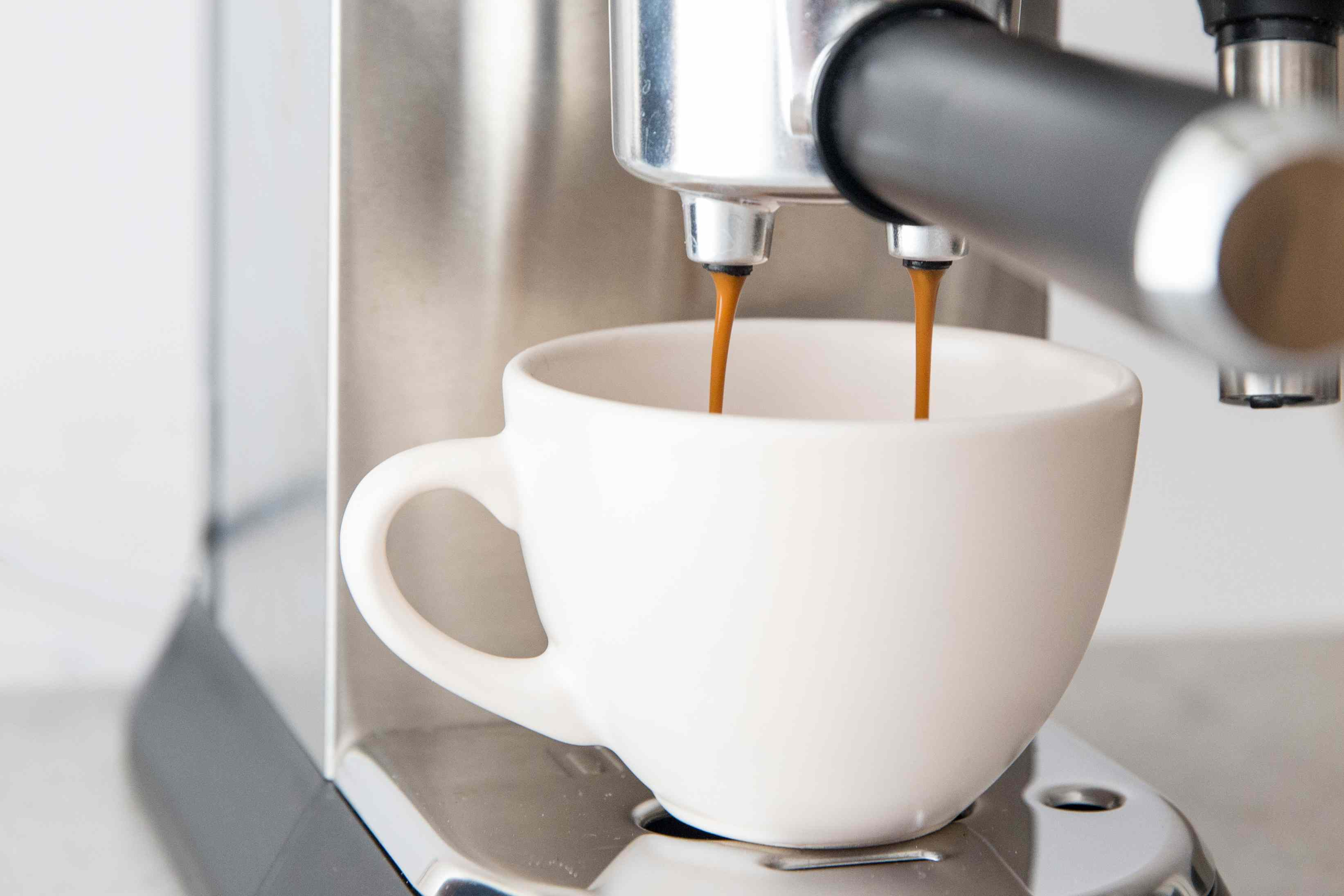 espresso pouring into a coffee cup from an espresso machine