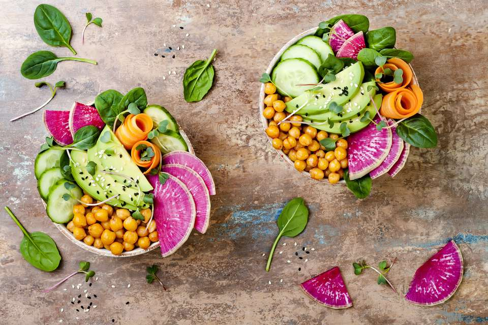 Raw vegan food bowls, with watermelon radish, chickpeas, and cucumbers