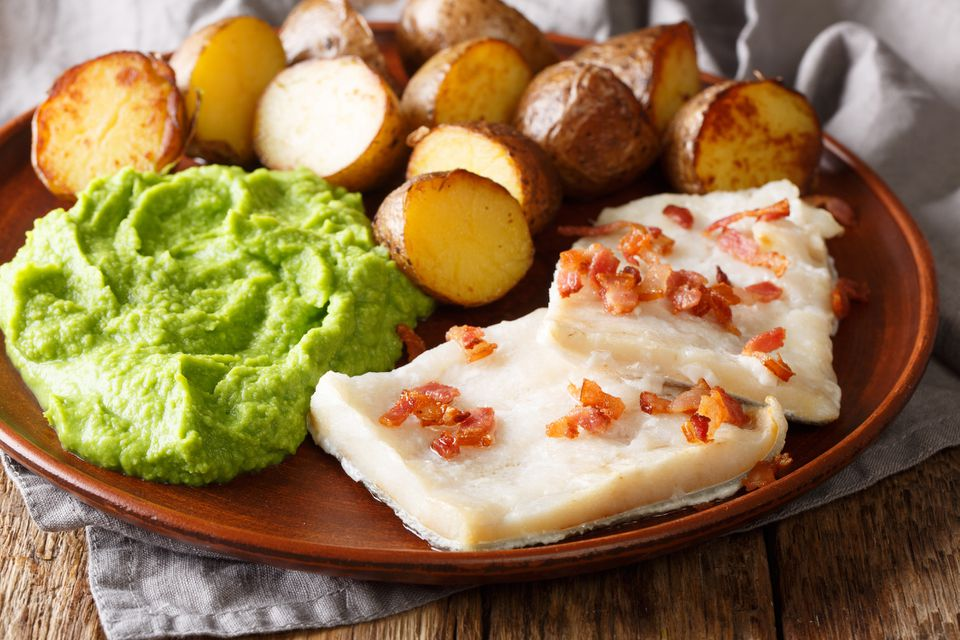 Cod lutefisk with pea puree, baked potatoes, and bacon—close-up on a plate
