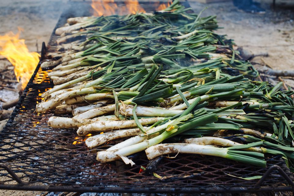 Spring onions on an open grill