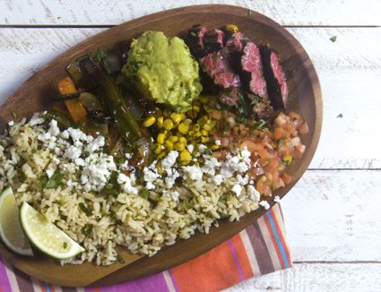Steak rice and guac on a wooden platter