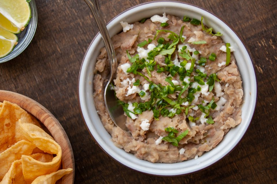 refried pinto beans garnished with queso cilantro and jalapeno