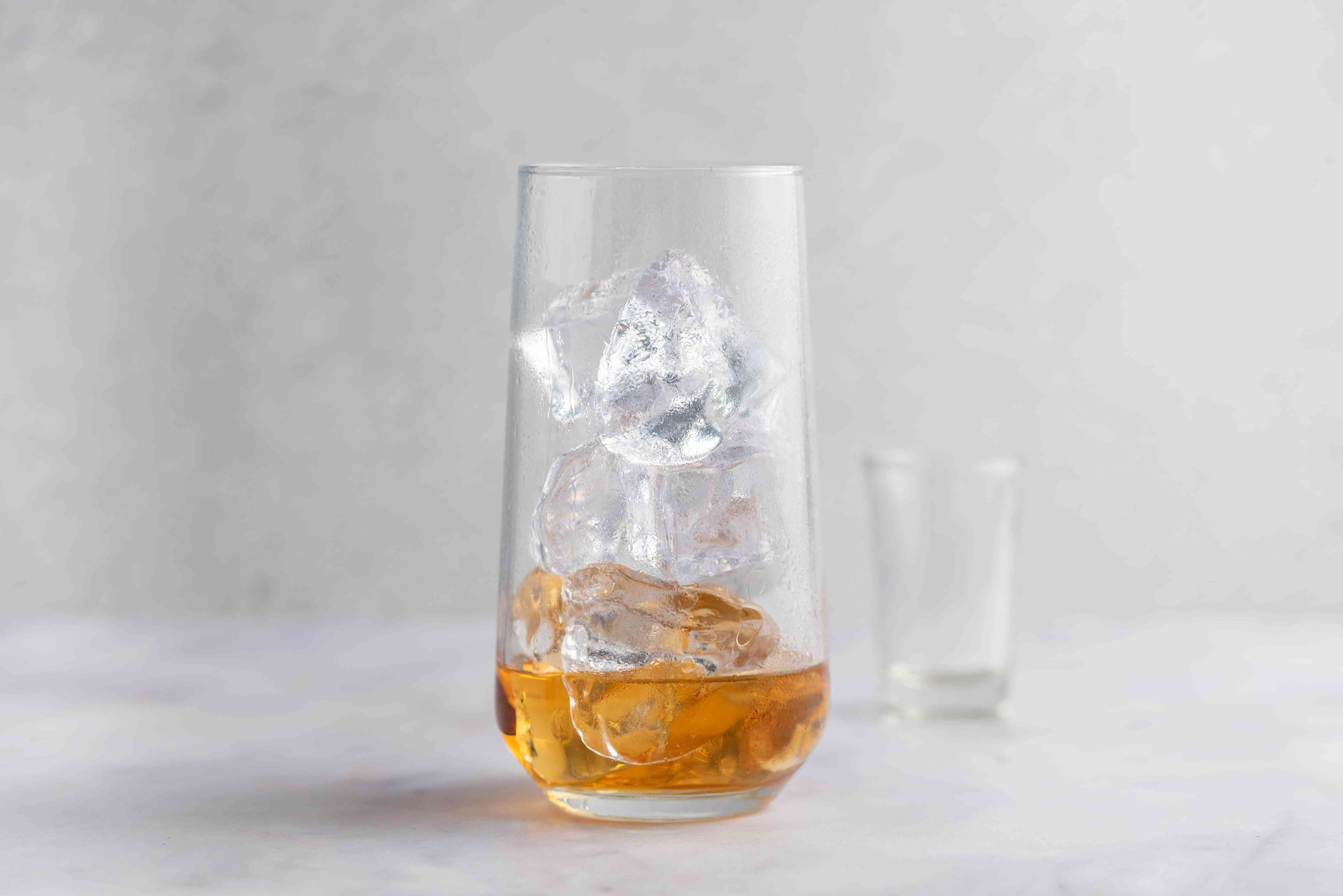 Pour the whiskey into a highball glass