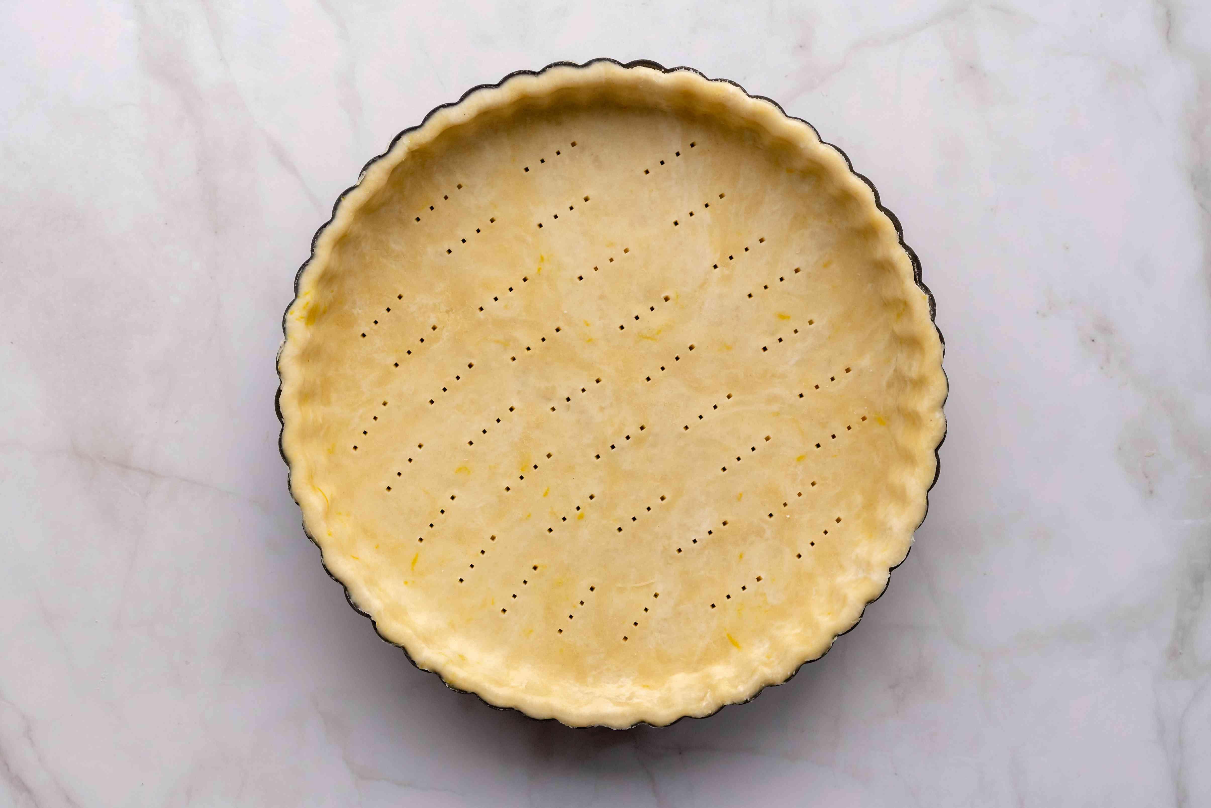 tart dough in a pan, prick the tart shell dough with a fork