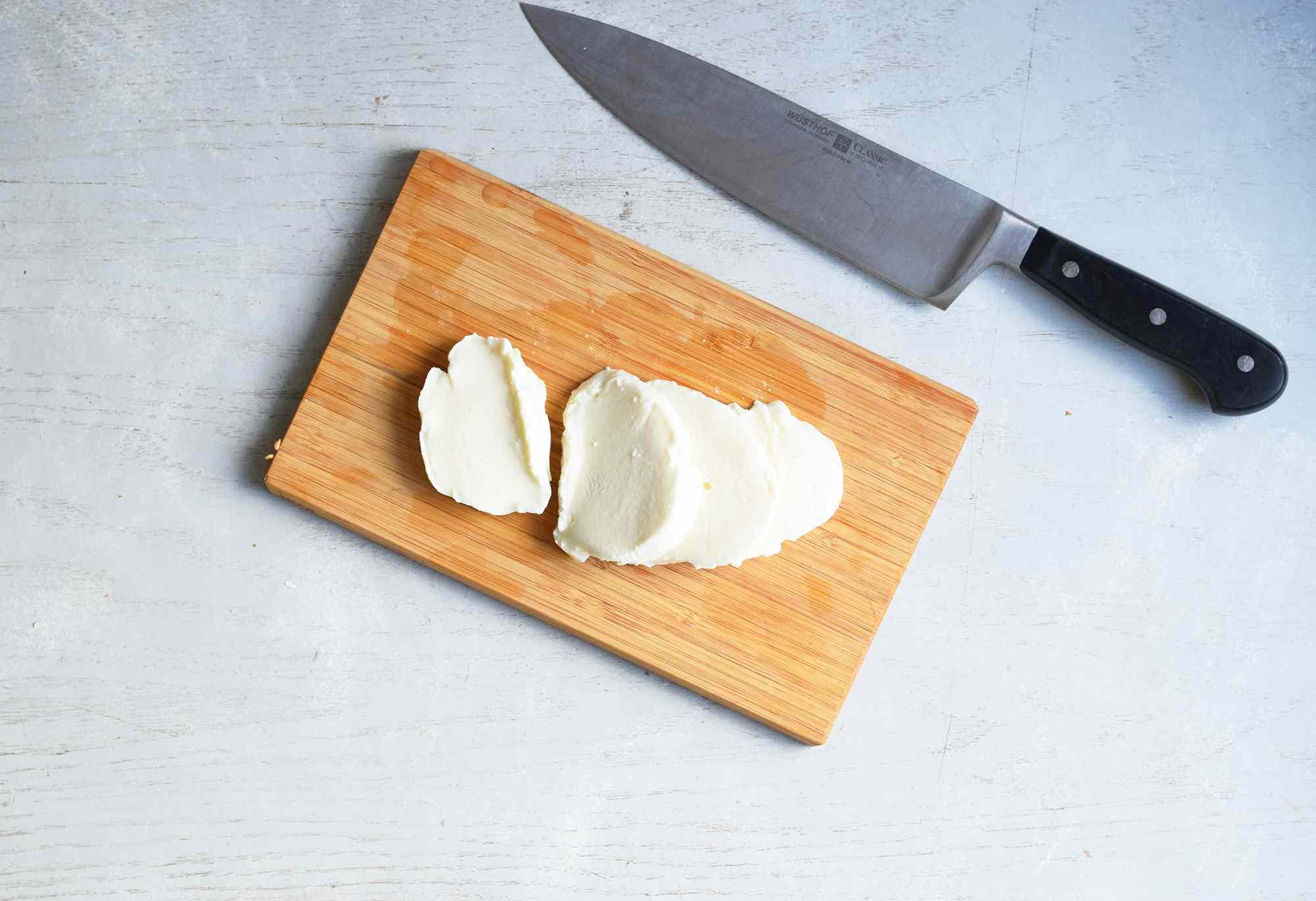 fresh mozzarella sliced on a cutting board