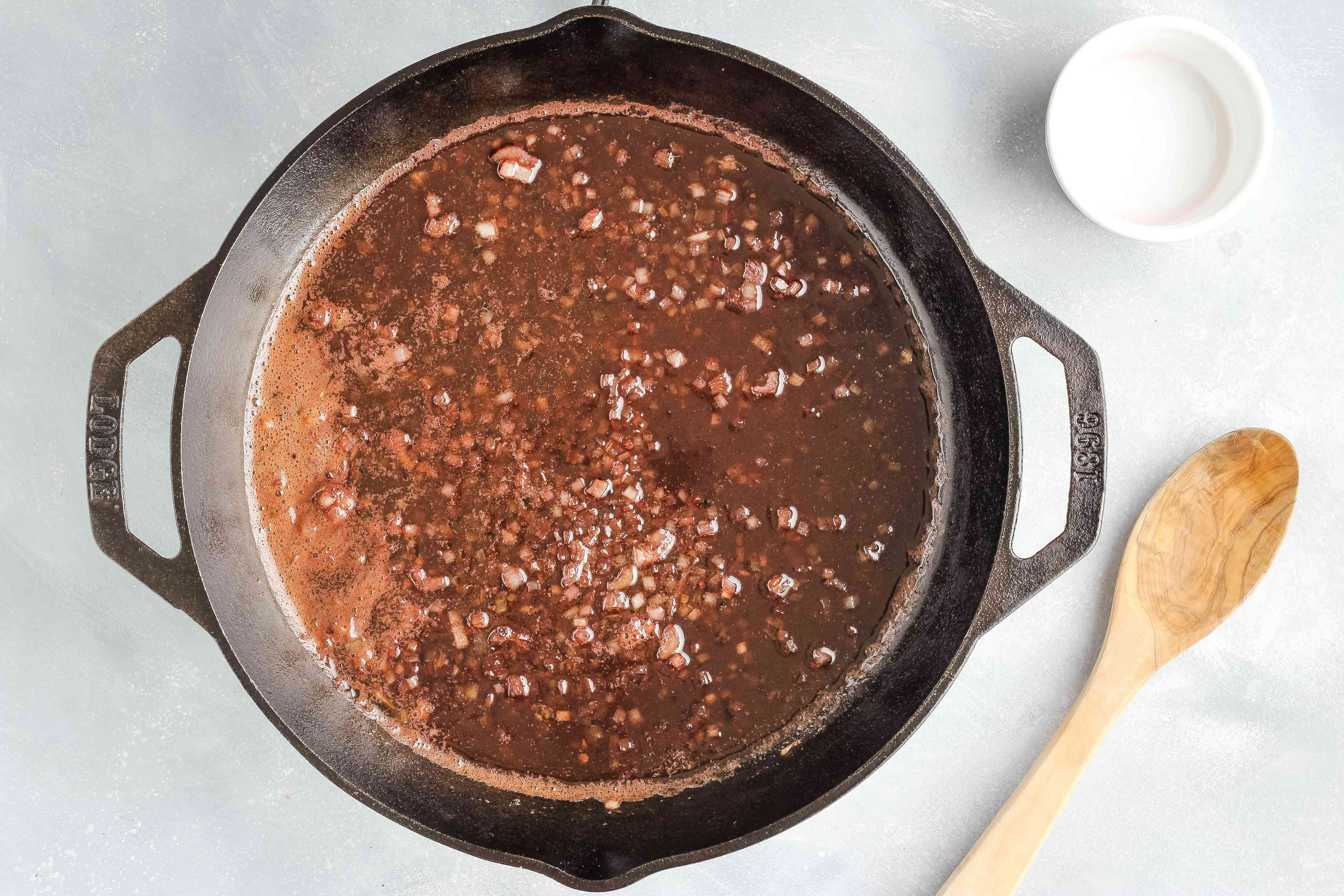 Bringing the wine sauce to a boil in a cast-iron skillet