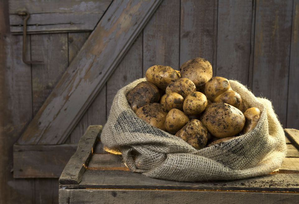 Potatoes in sack on wood