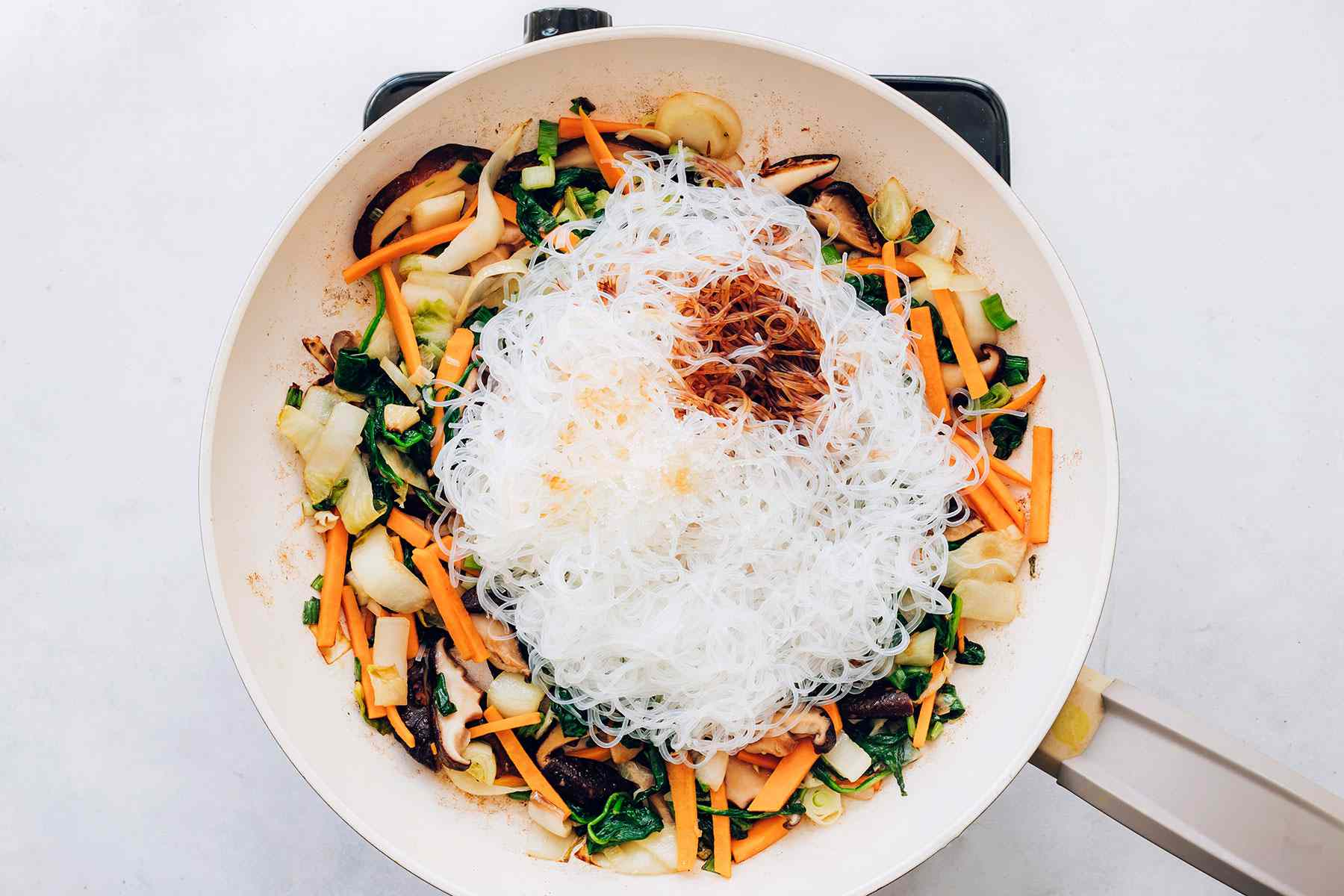 vegetables, noodles, and sauce in a pan