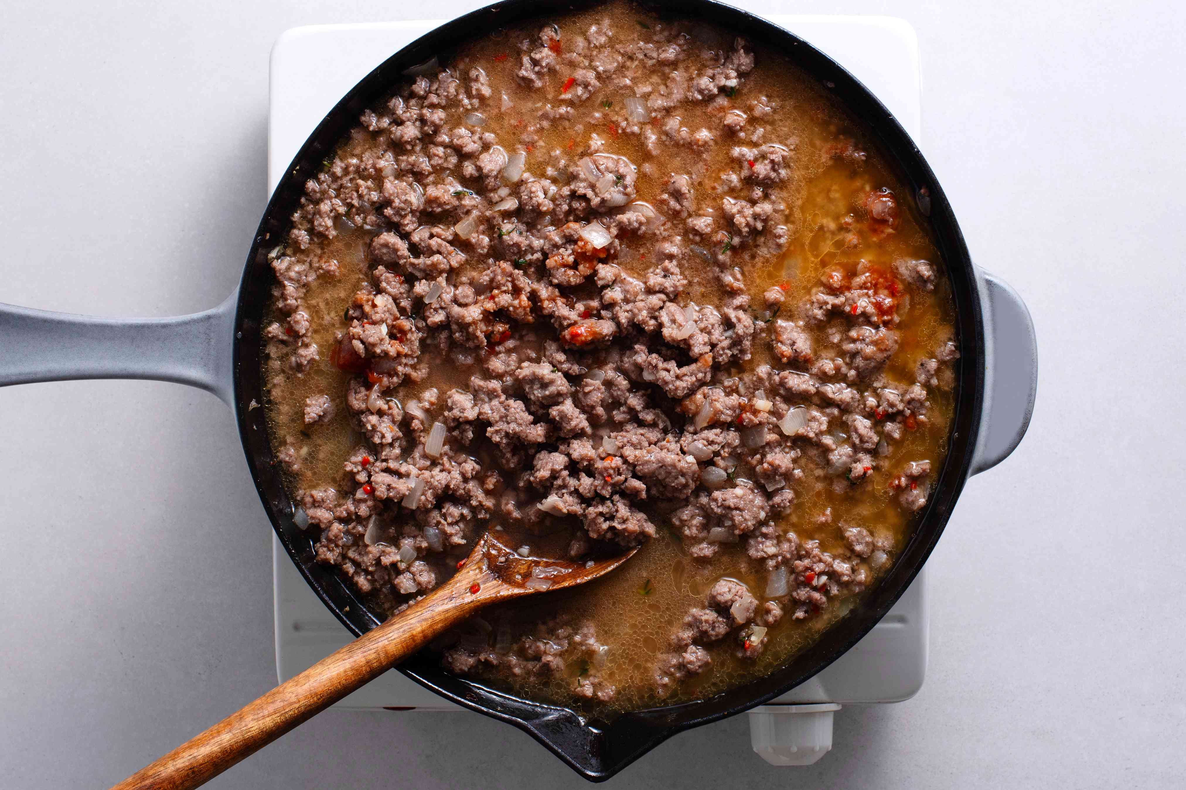 seasoned beef with water in a pan