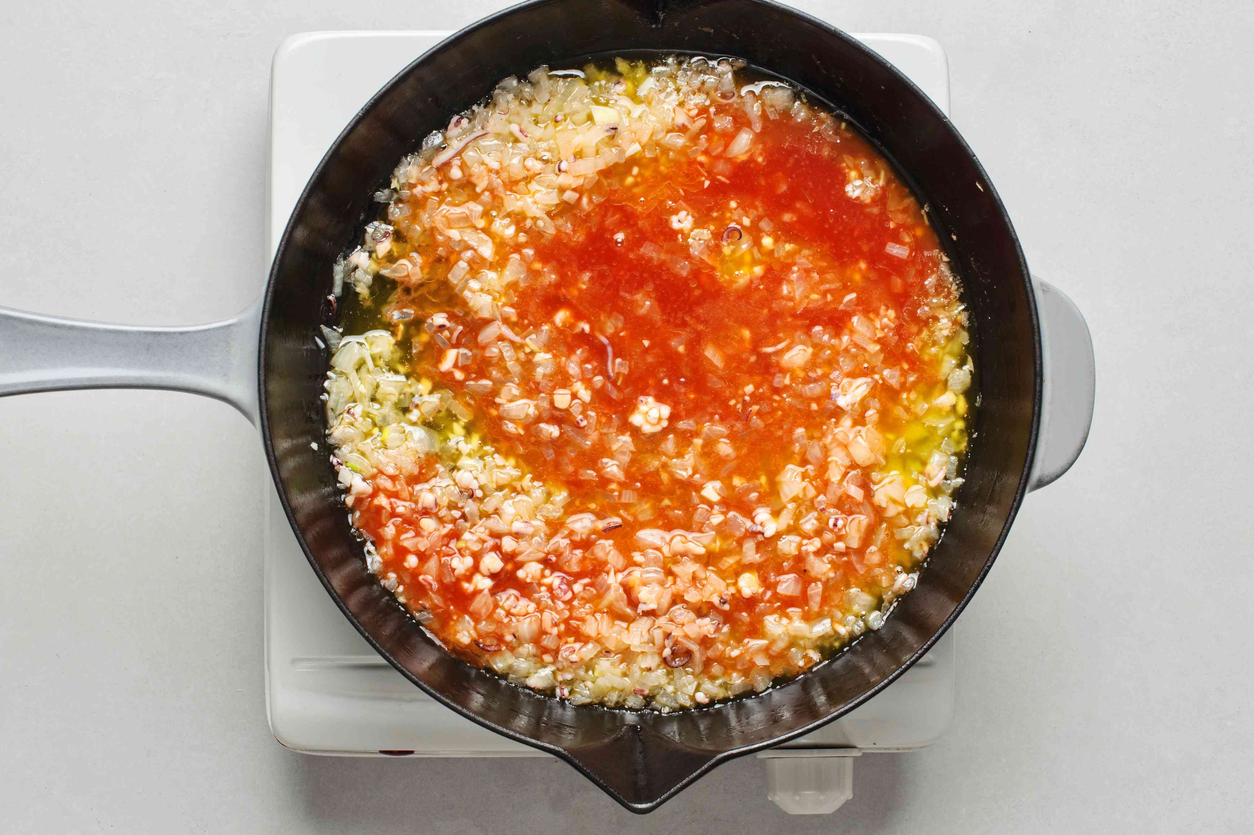 A pan with tomato mixture, cooked onions, and tentacles