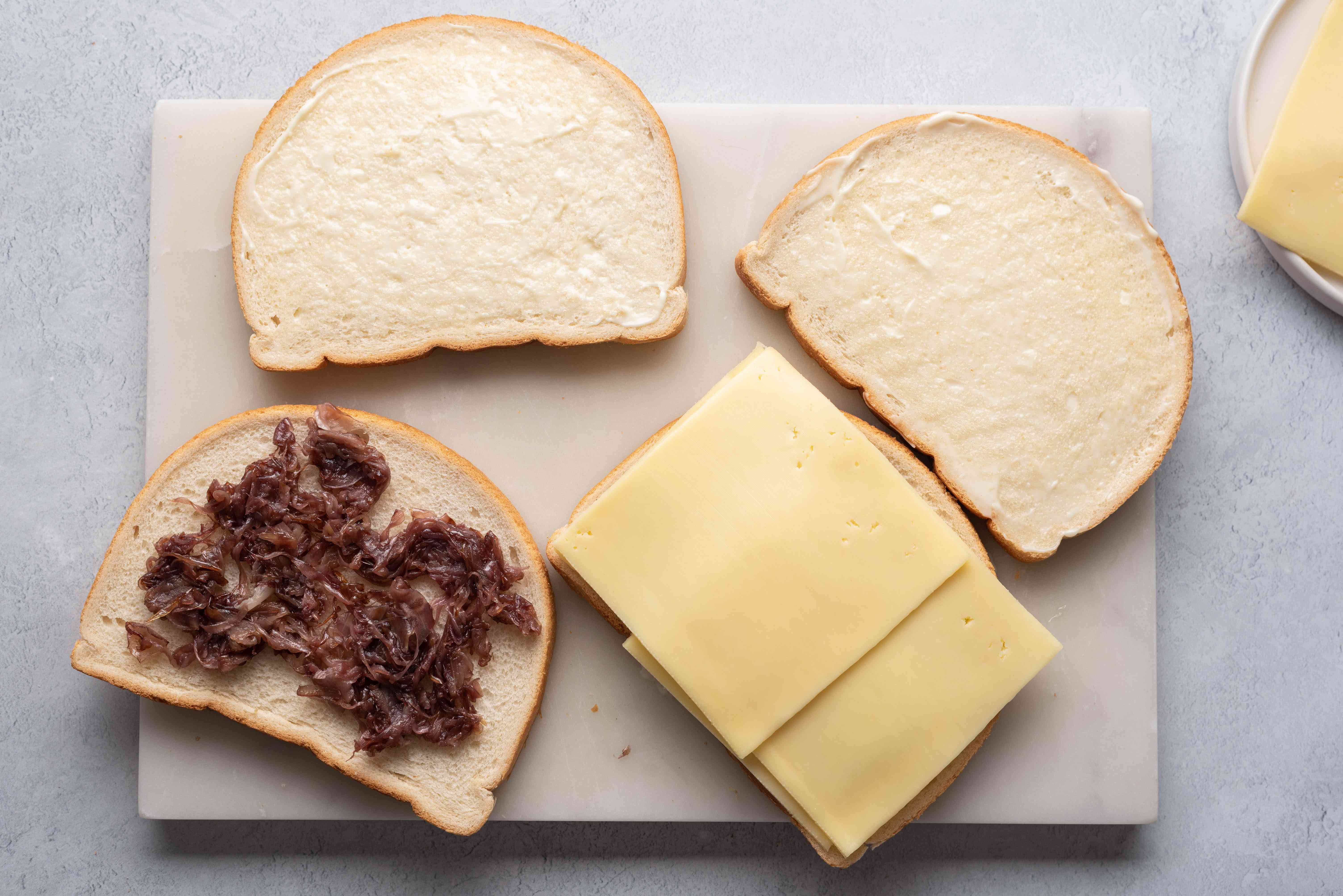 bread slices being topped with caramelized onion on one side and cheese on the other