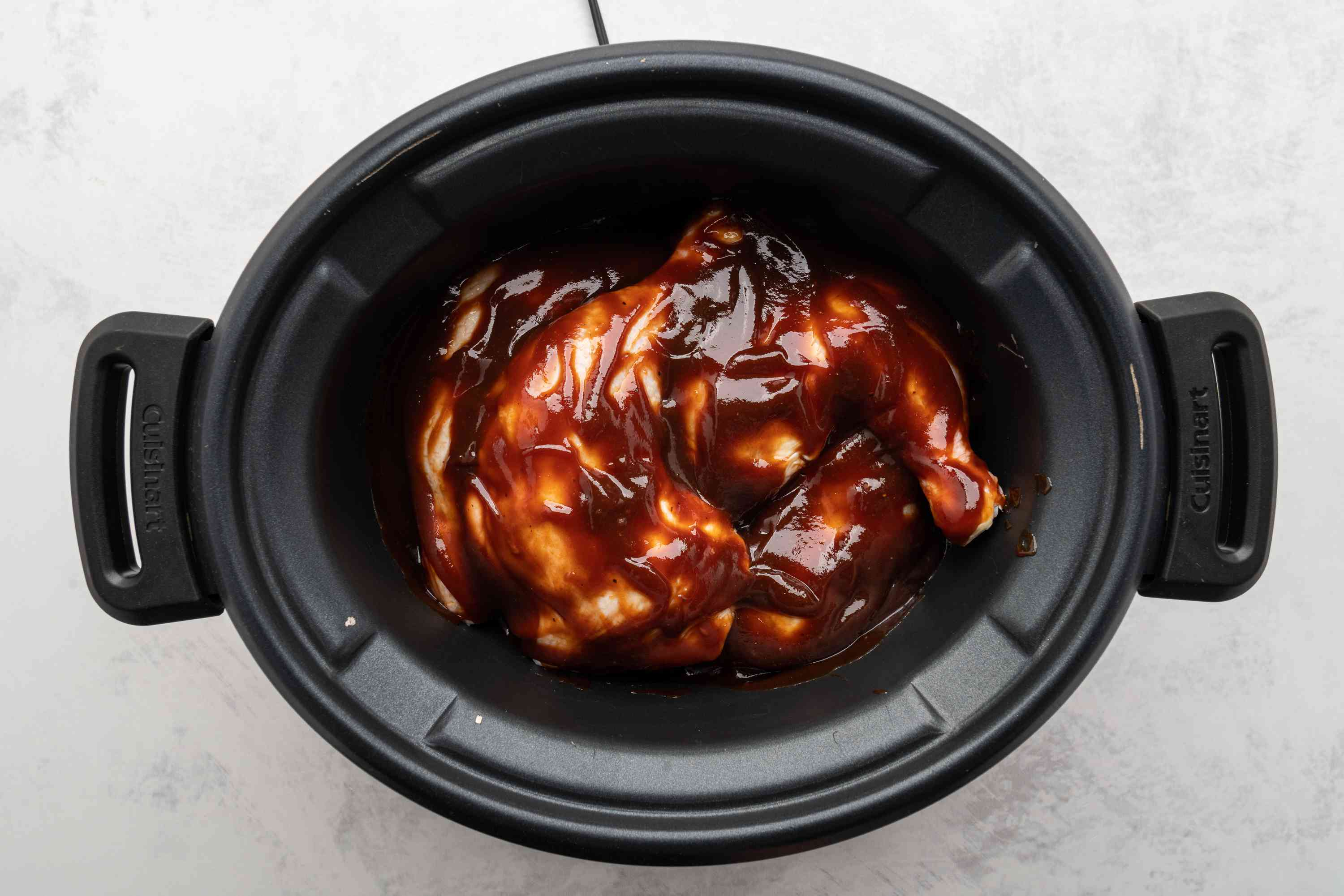 Pour barbecue sauce over chicken legs in the slow cooker