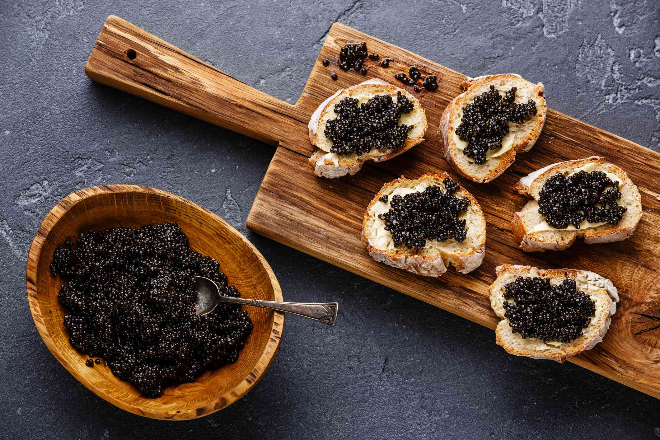 Sturgeon black caviar in wooden bowl and sandwiches