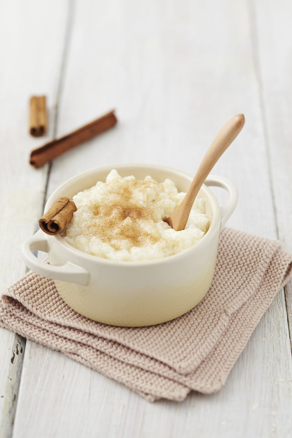Milk rice pudding in pot with cinnamon on table