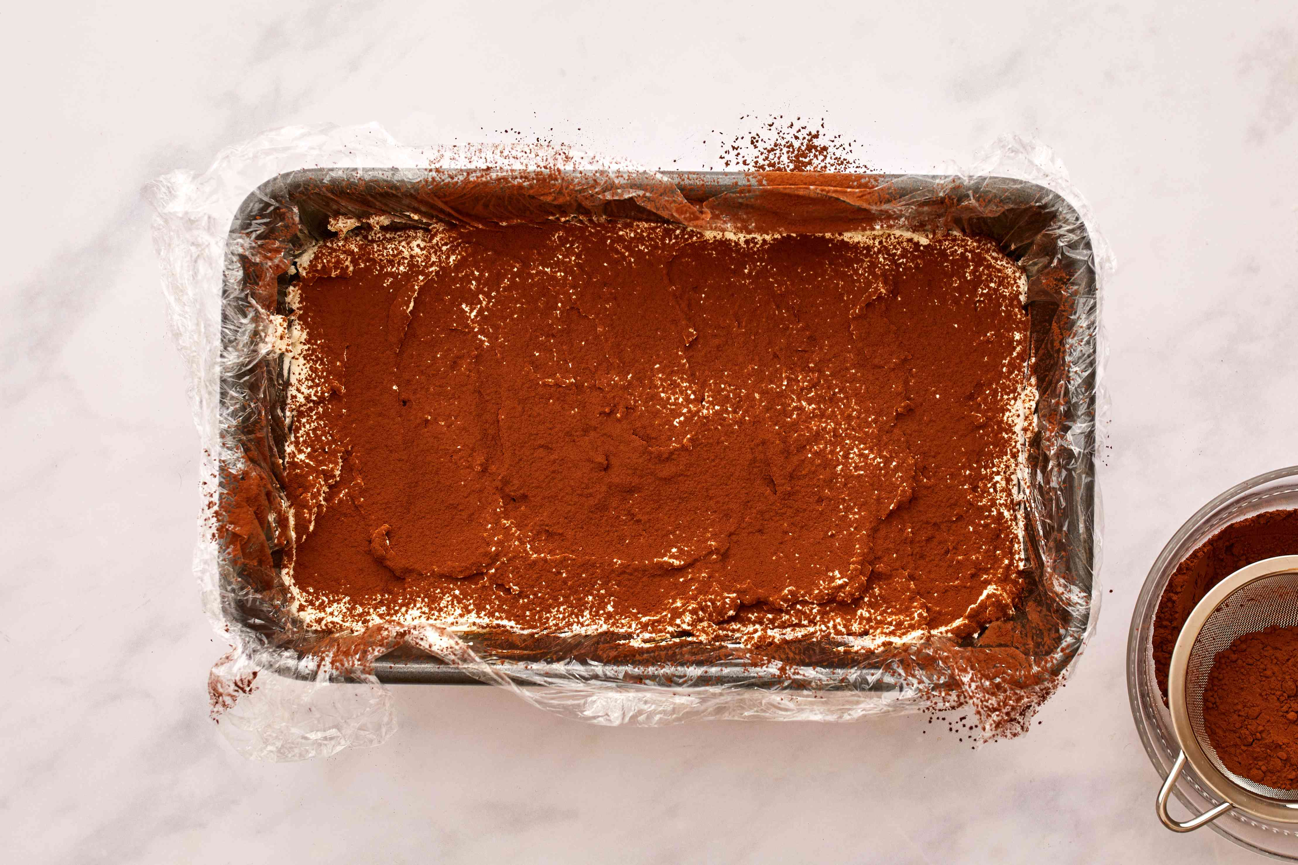 each layer of tiramisu being sprinkled with cocoa powder