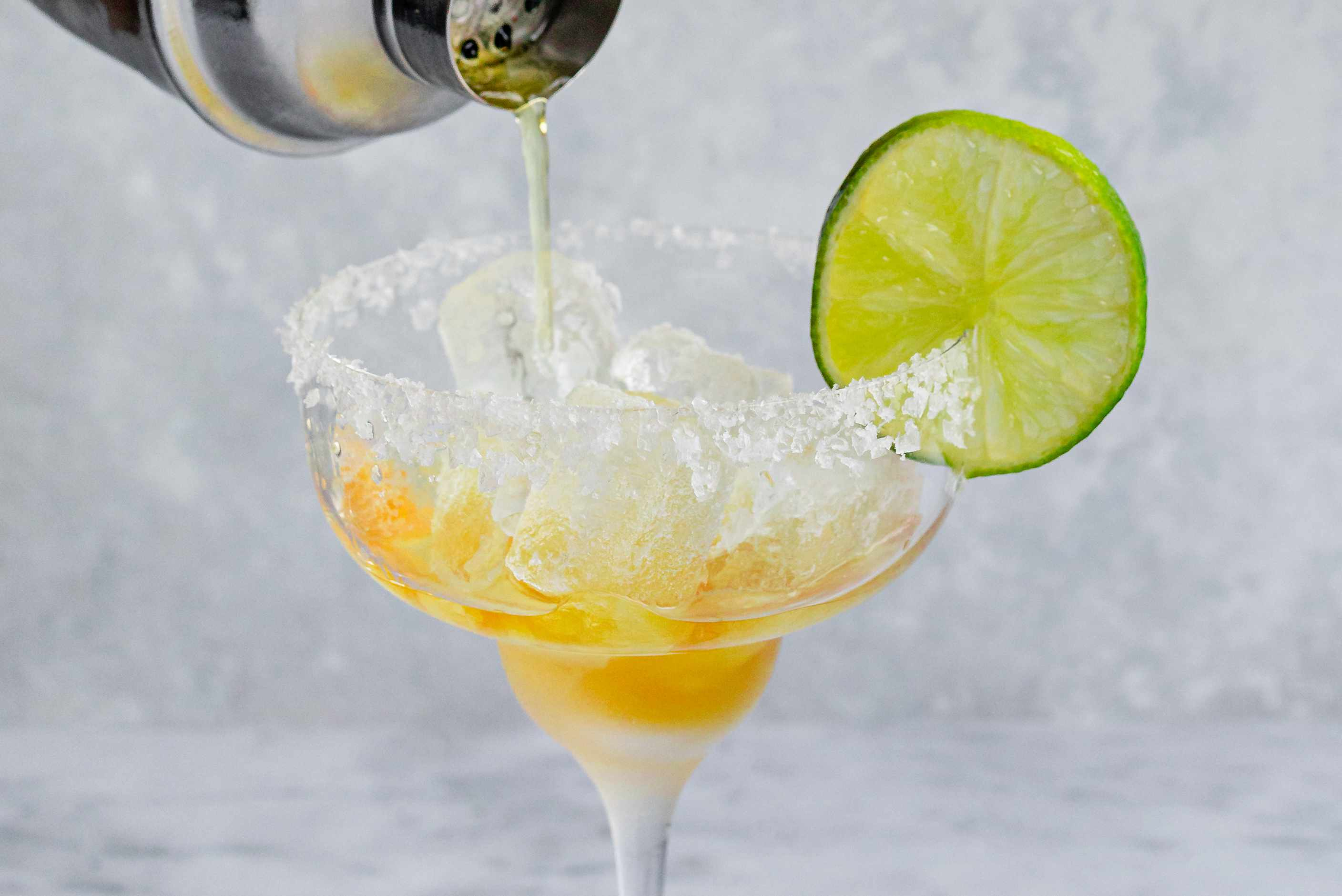 Cadillac margarita strained into a prepared glass rimmed with salt and a slice of lime